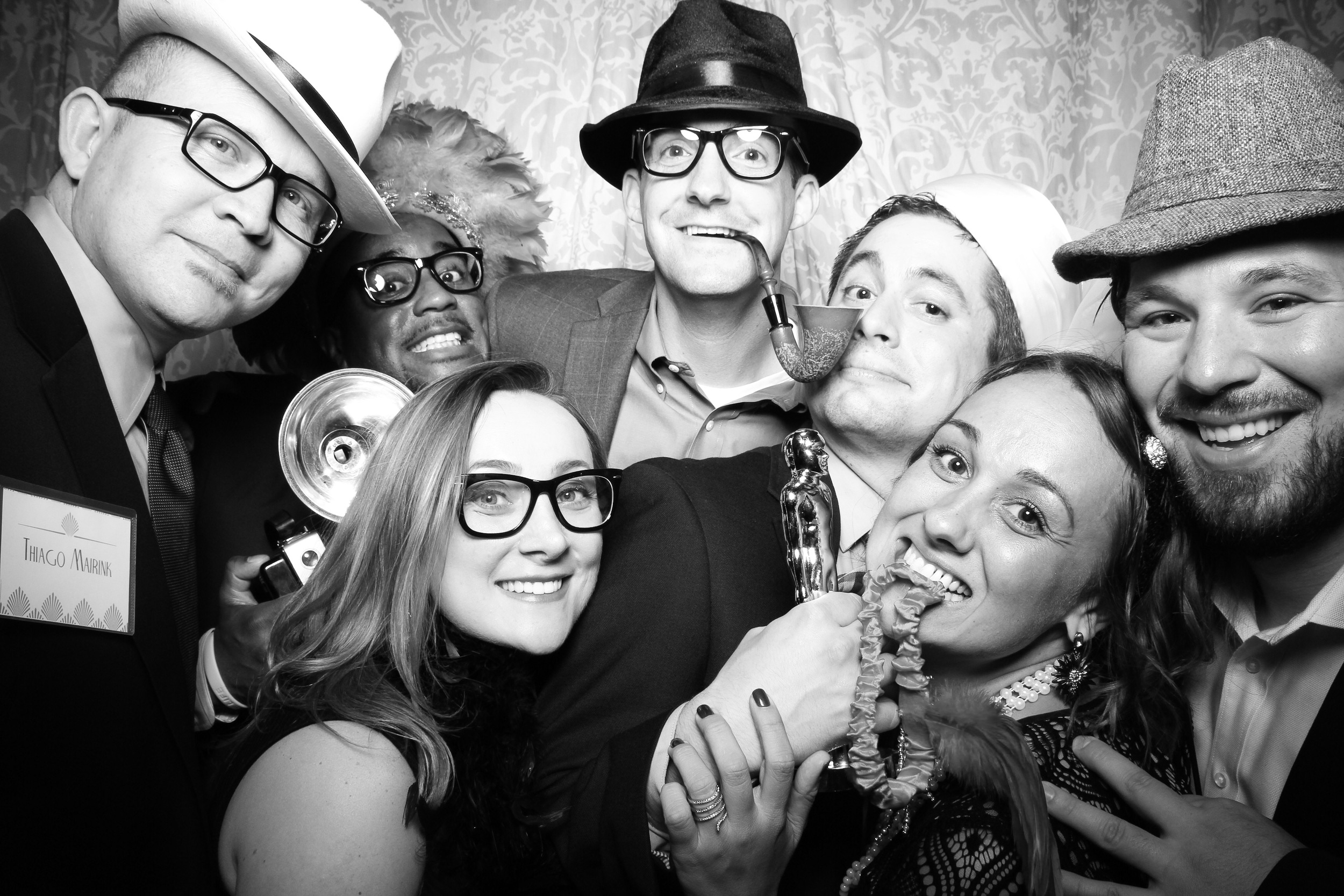Corporate event guests takes a fun photo booth group shot with vintage style 20s props at the Union League Club of Chicago!