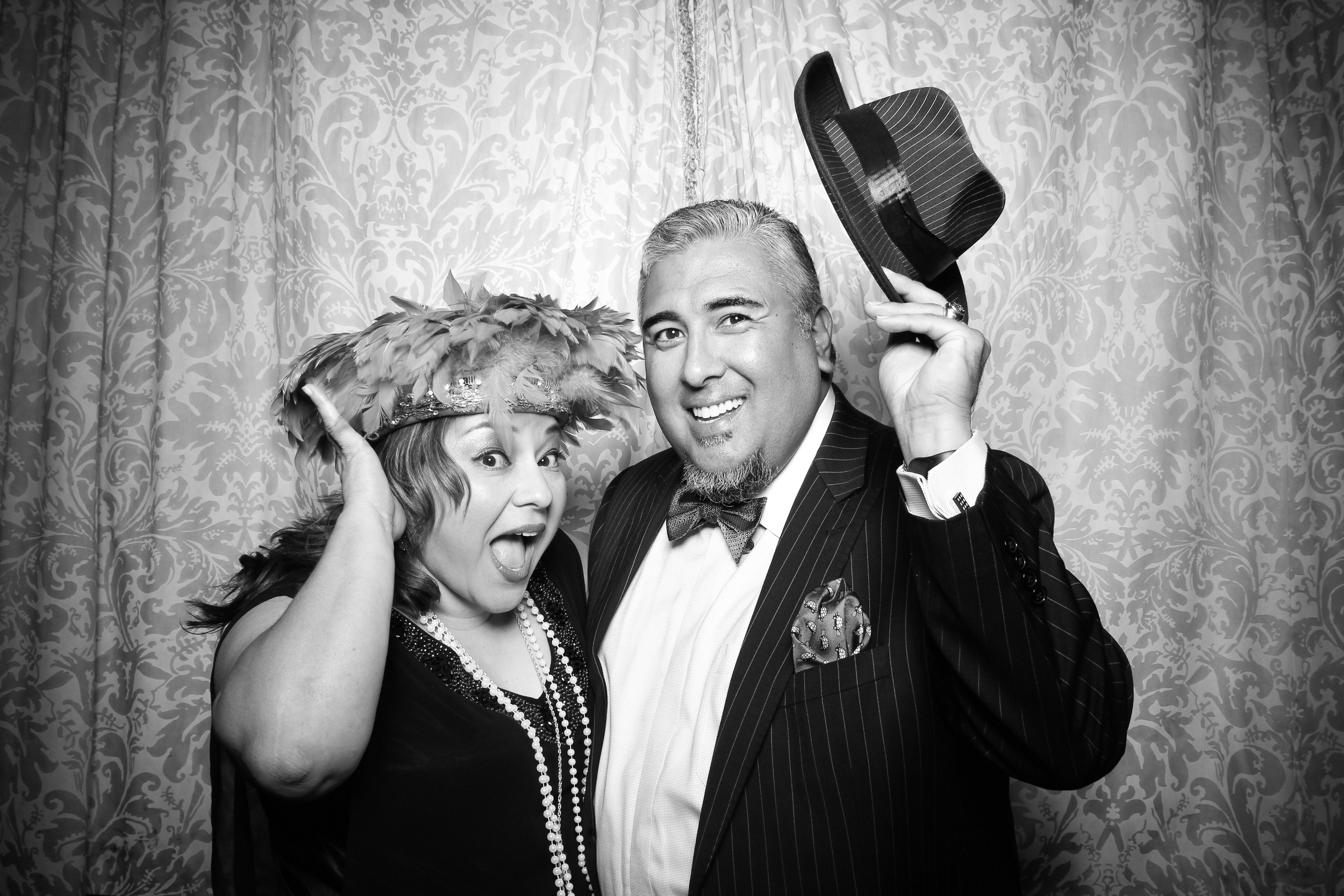 A couple takes a fun photo booth portrait with Great Gatsby style event props!