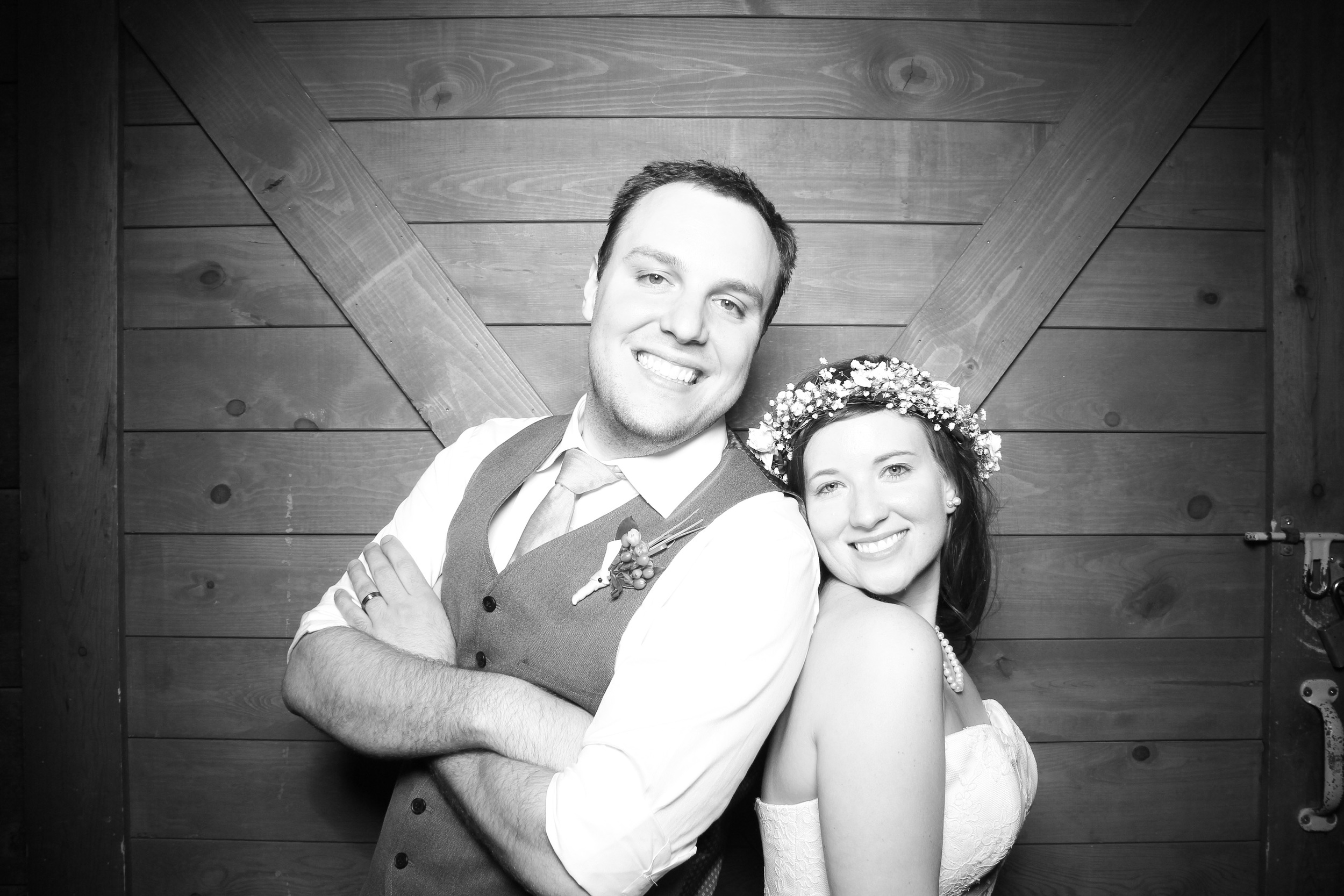 The bride and groom take a photo booth picture at Hoosier Grove Barn with the rustic barn door backdrop!