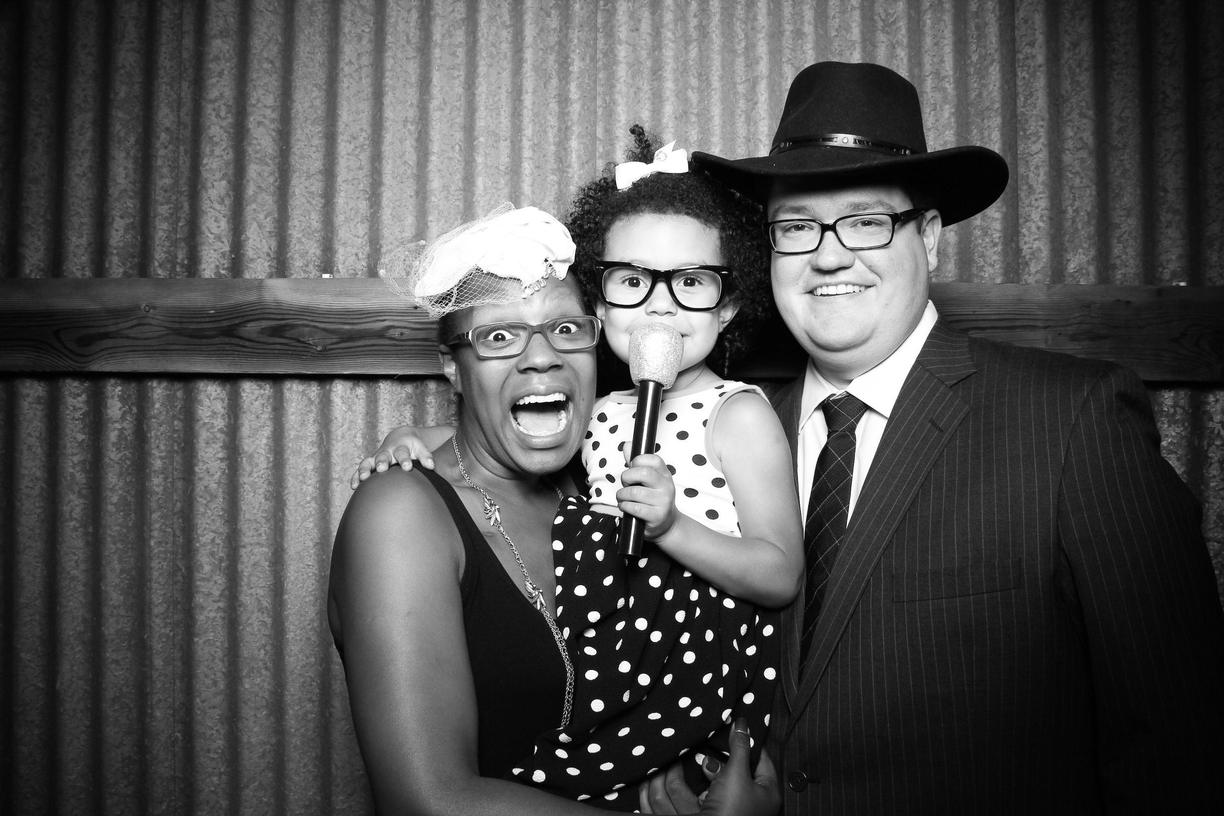 Wedding guests take a fun photo booth picture with the vintage props at the Mora Farm in Waterman, IL.