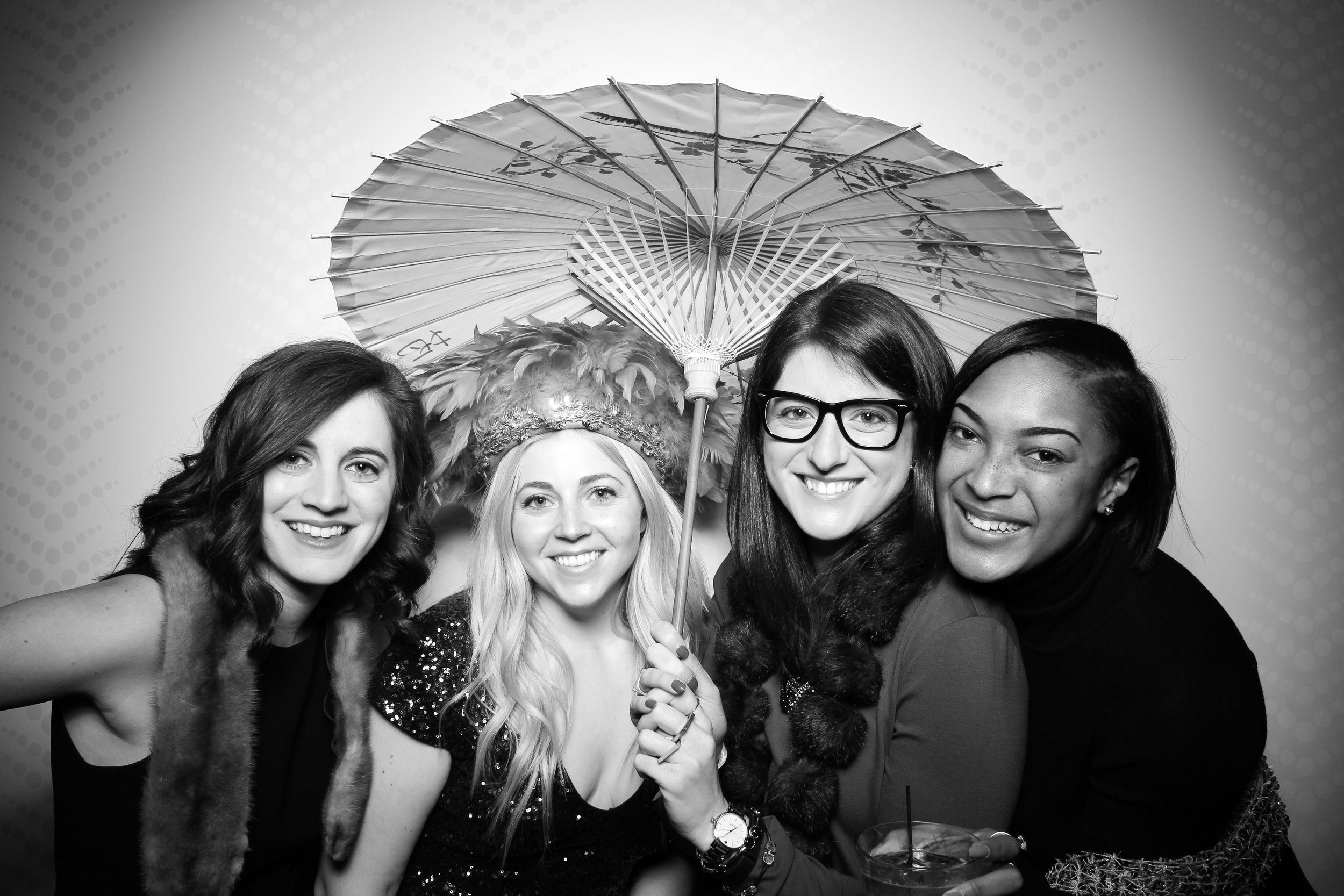 Guests use a vintage parasol photo booth prop at a company holiday party at Hotel Palomar in Chicago!