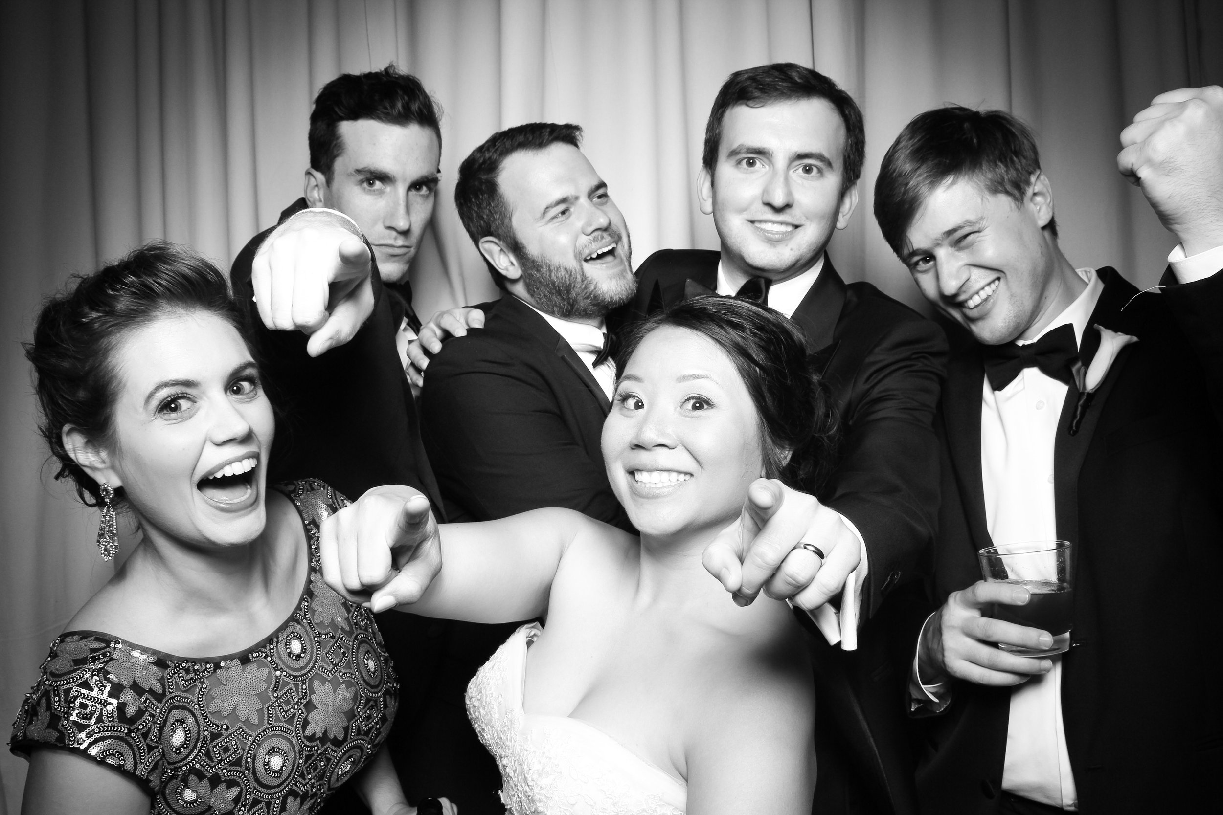 The bride and groom pose for a photo booth picture with friends in the Rookery lobby!