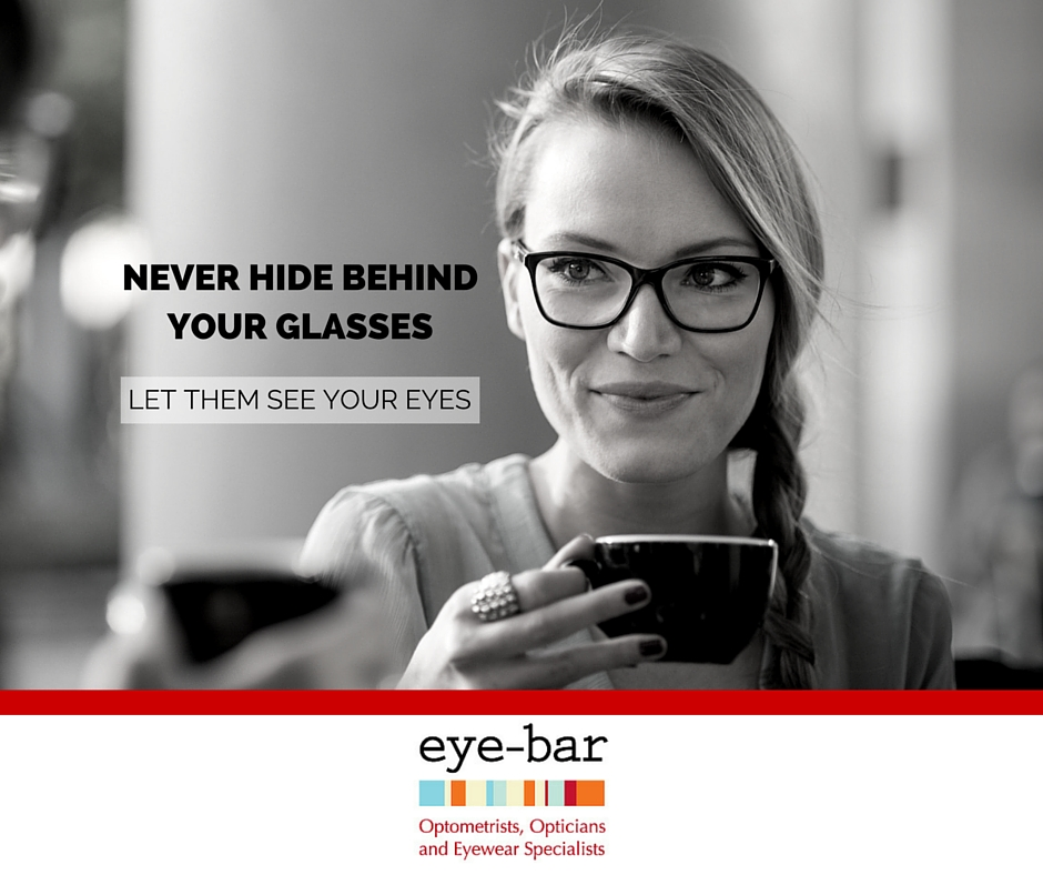 Lady drinking coffee wearing black framed eyeglasses with non-glare lenses. Text in image says: Never hide behind your glasses. Let them see your eyes.