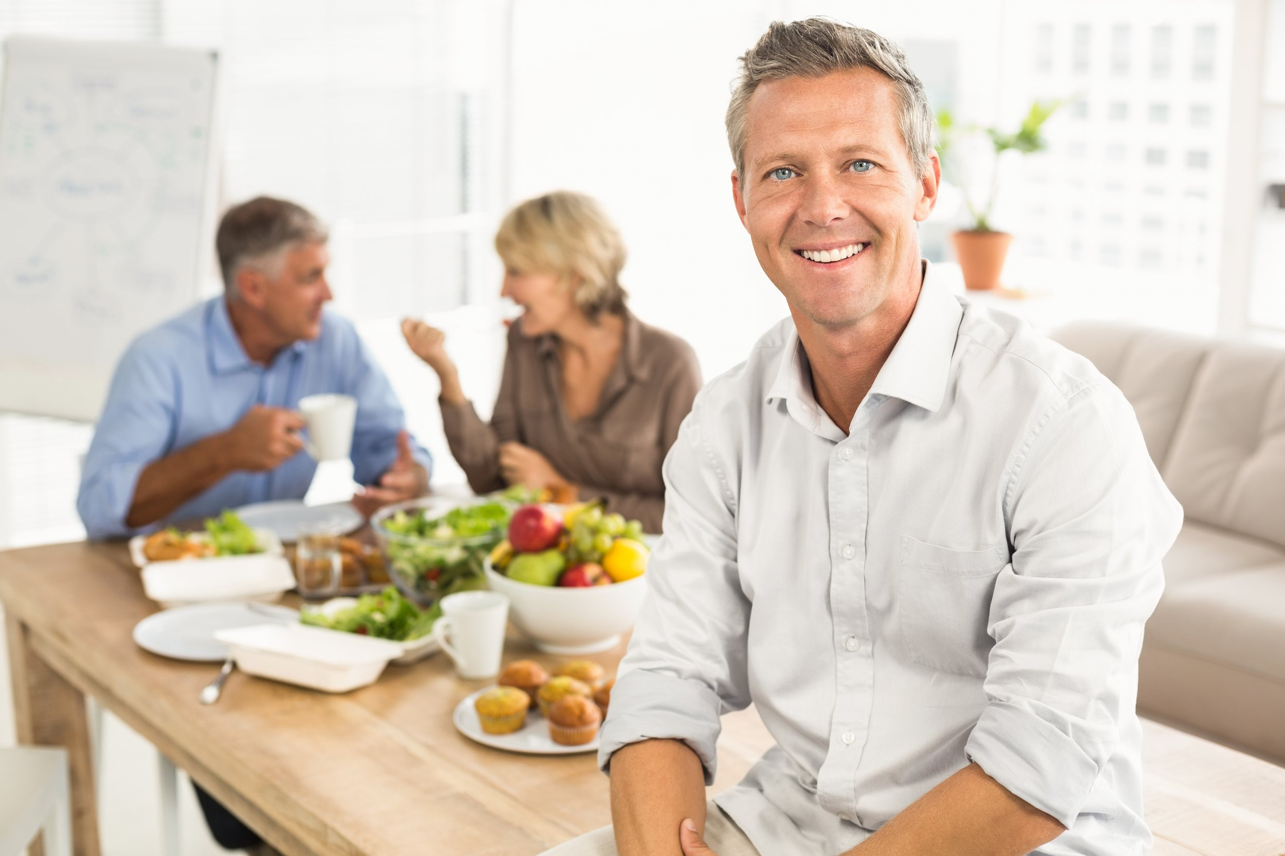 Smiling casual businessman sitting on table at lunch