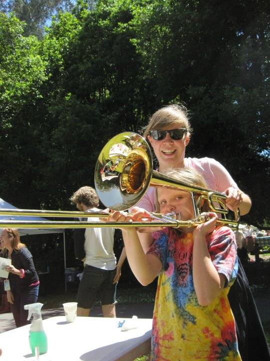Annie shows a visitor the art of the brass family on a trombone