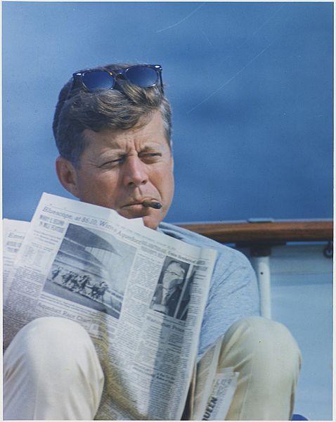 0. Hyannisport_Weekend._President_Kennedy_with_cigar_and_New_York_Times._Hyannisport,_MA,_aboard_the_-Honey_Fitz-._-_NARA_-_194268.jpg