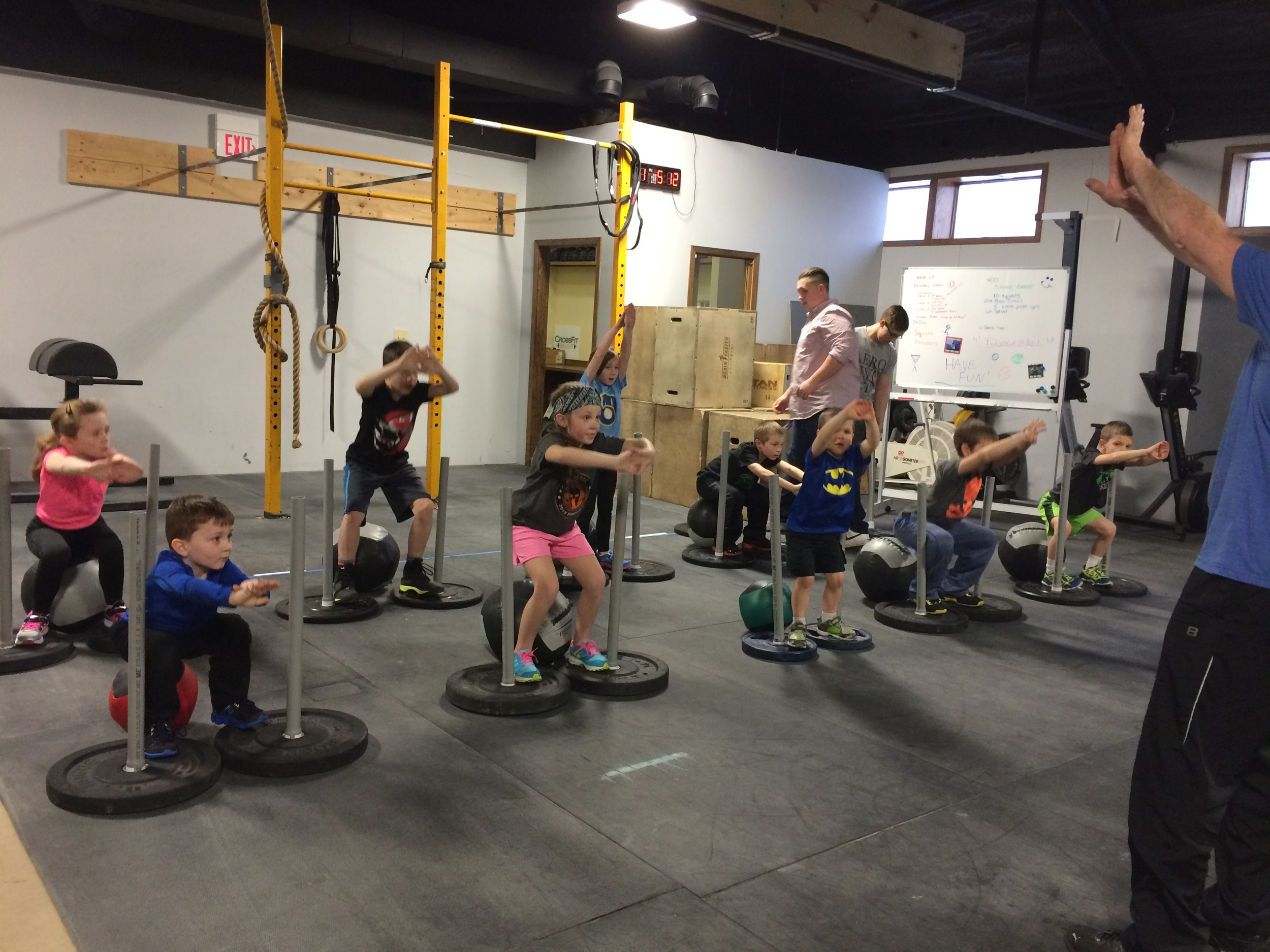 Coach Mike leading on our Rock Star CrossFit Kids on proper Squat form.