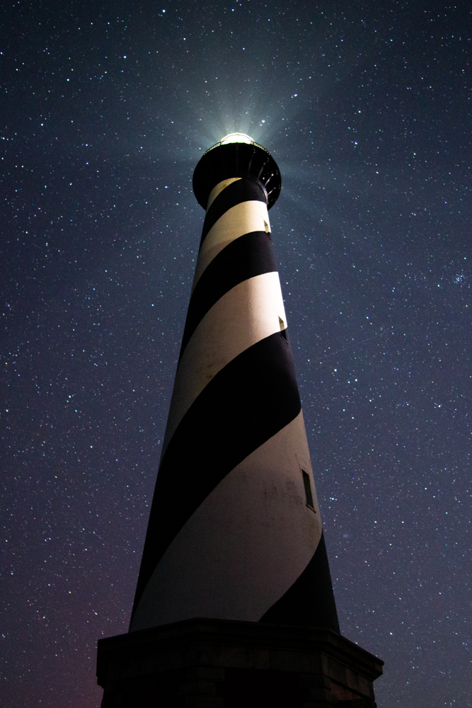 Cape Hatteras Lighthouse under the night sky in Outer Banks, North Carolina.