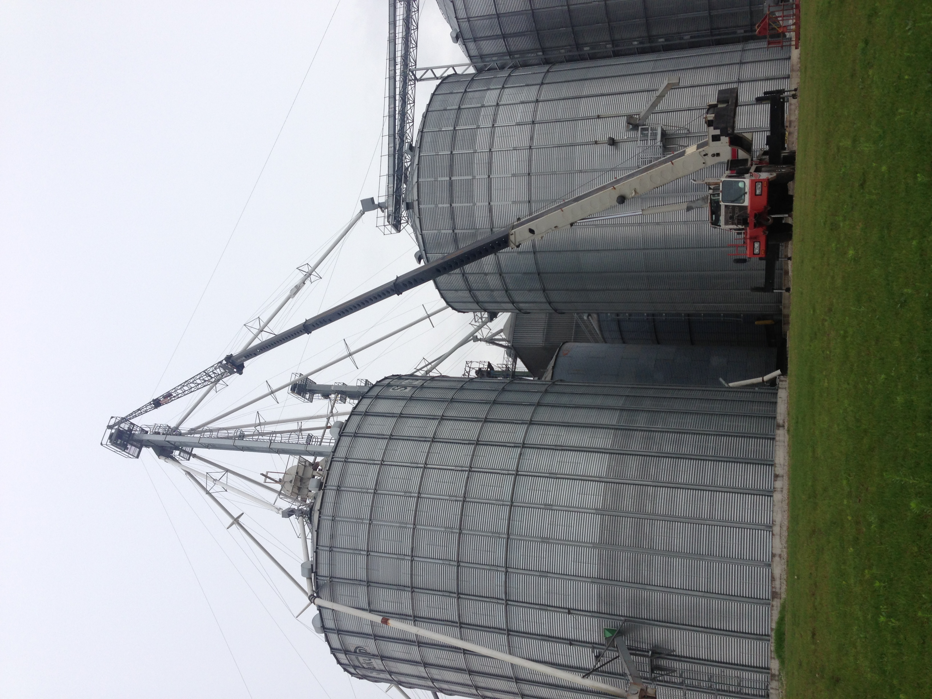 Grain bin spout lifted by mobile crane