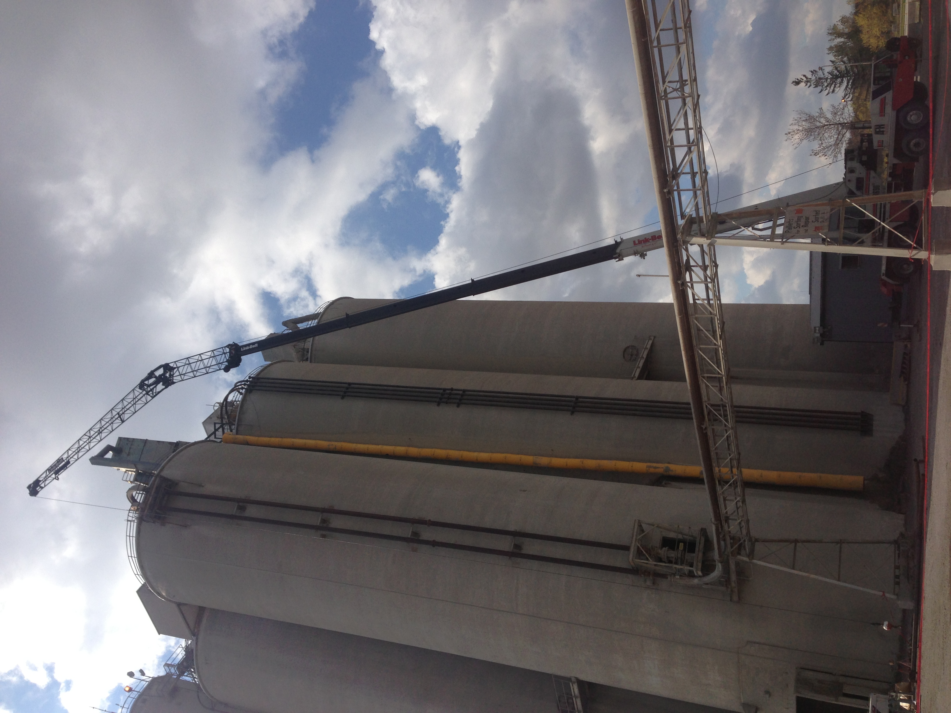 Steel pipe being lifted by mobile crane on silo roof
