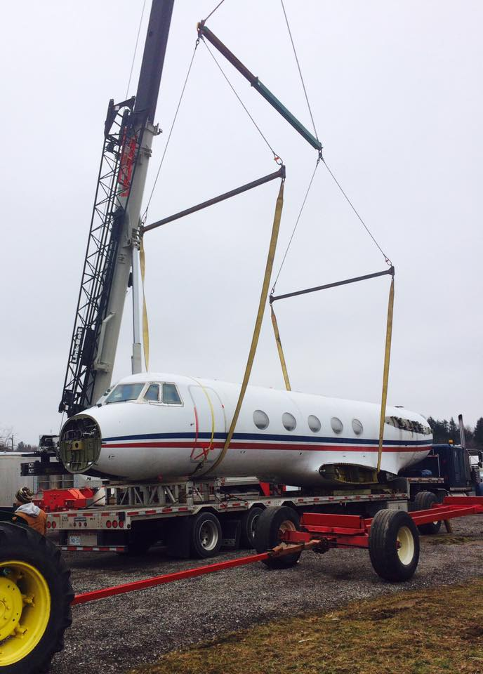 Plane fuselage being lifted by mobile crane