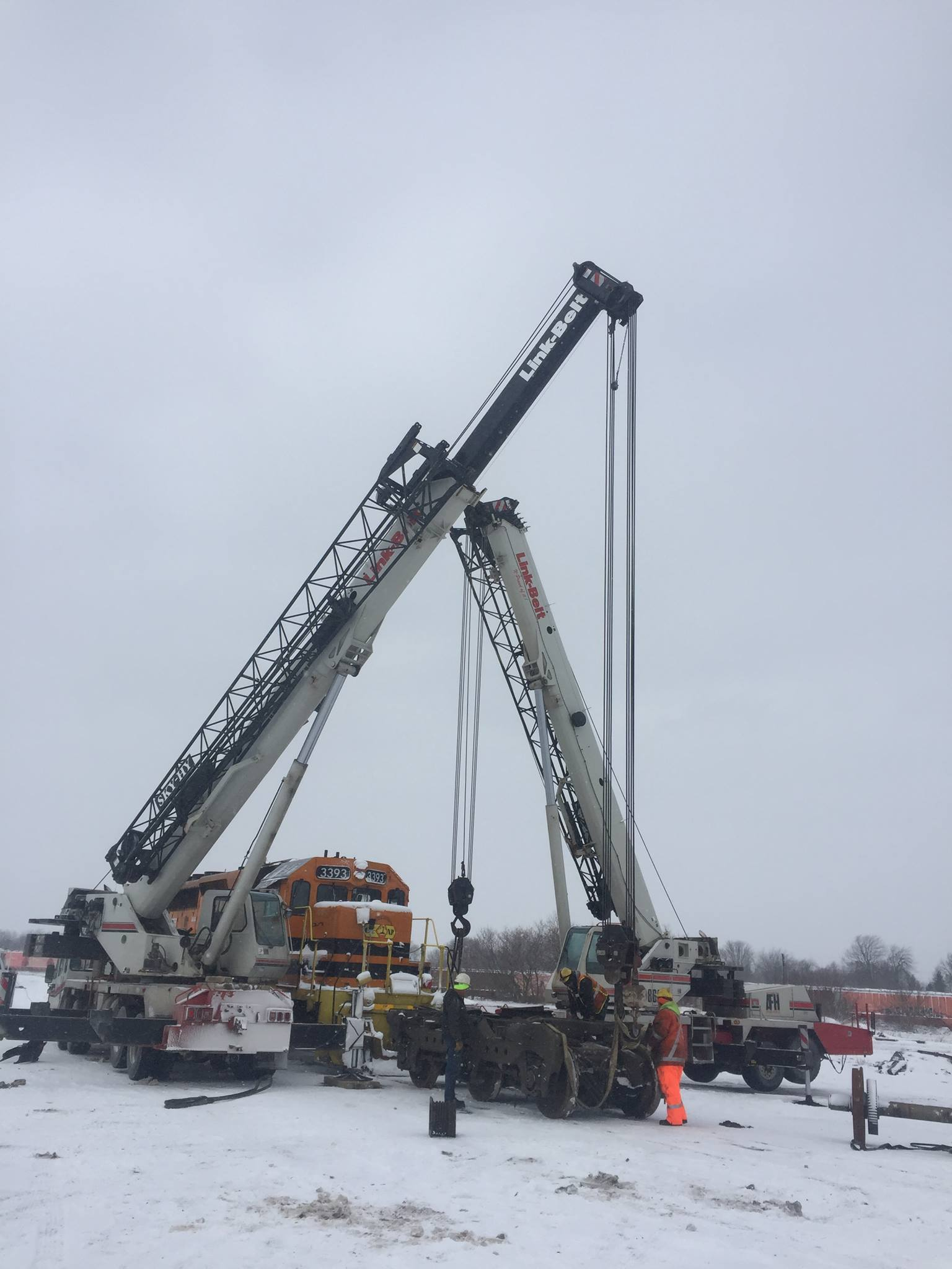 2 mobile cranes lift train car to rebuild motor