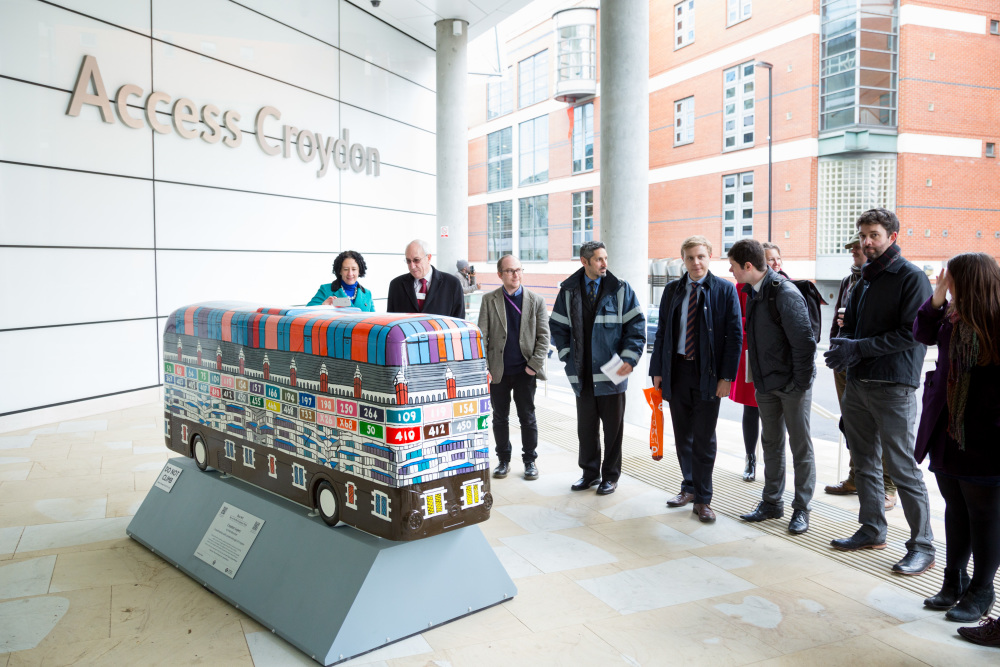 people looking at a bus sculpture