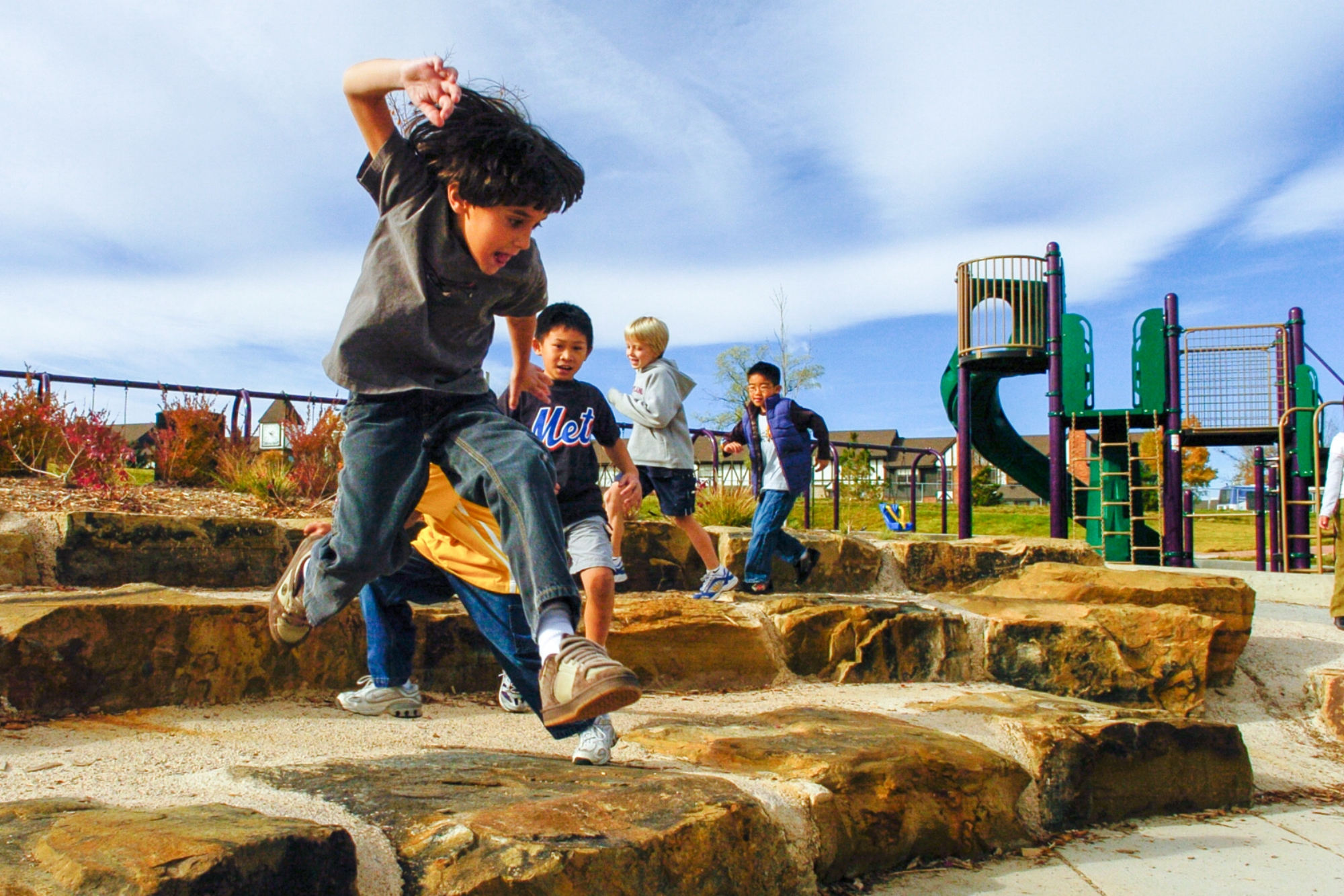 Denver Public Schools Learning Landscapes at Southmoor Elementary kid playing on boulder rock outdoor classroom amphitheater at playground