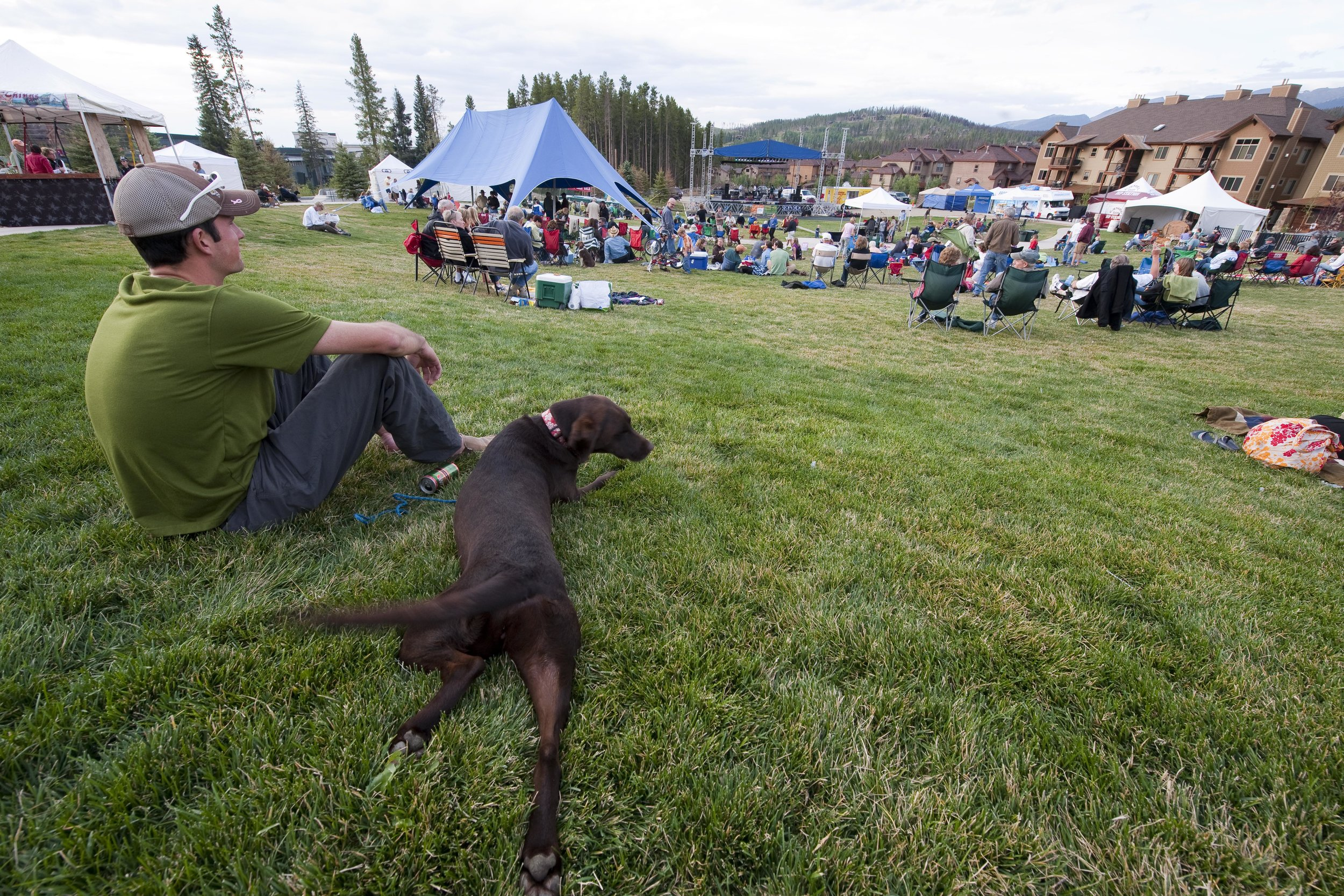 Guy with dog sitting on grass lawn amphitheater seating watching a concert festival stage in winter park colorado