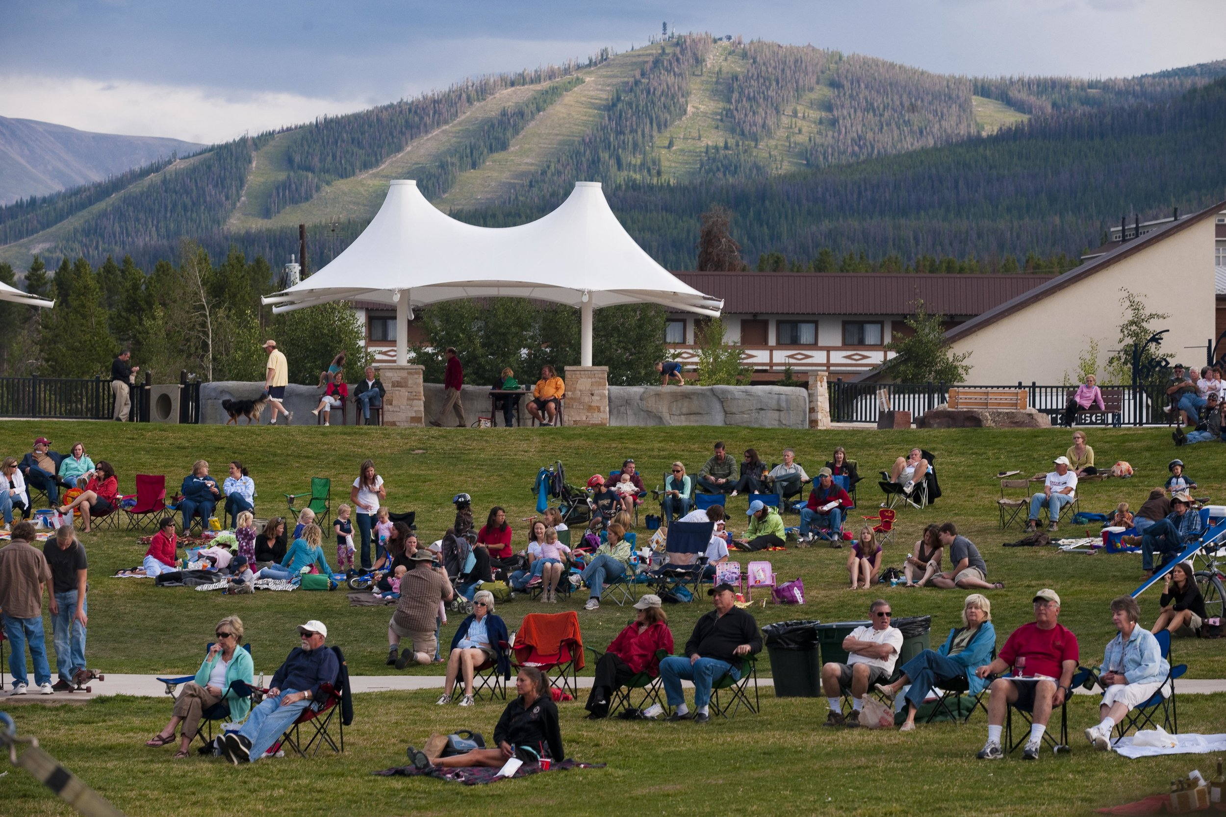 People sitting watching on grass lawn amphitheater concert venue for music festival in winter park Colorado with mountains in back