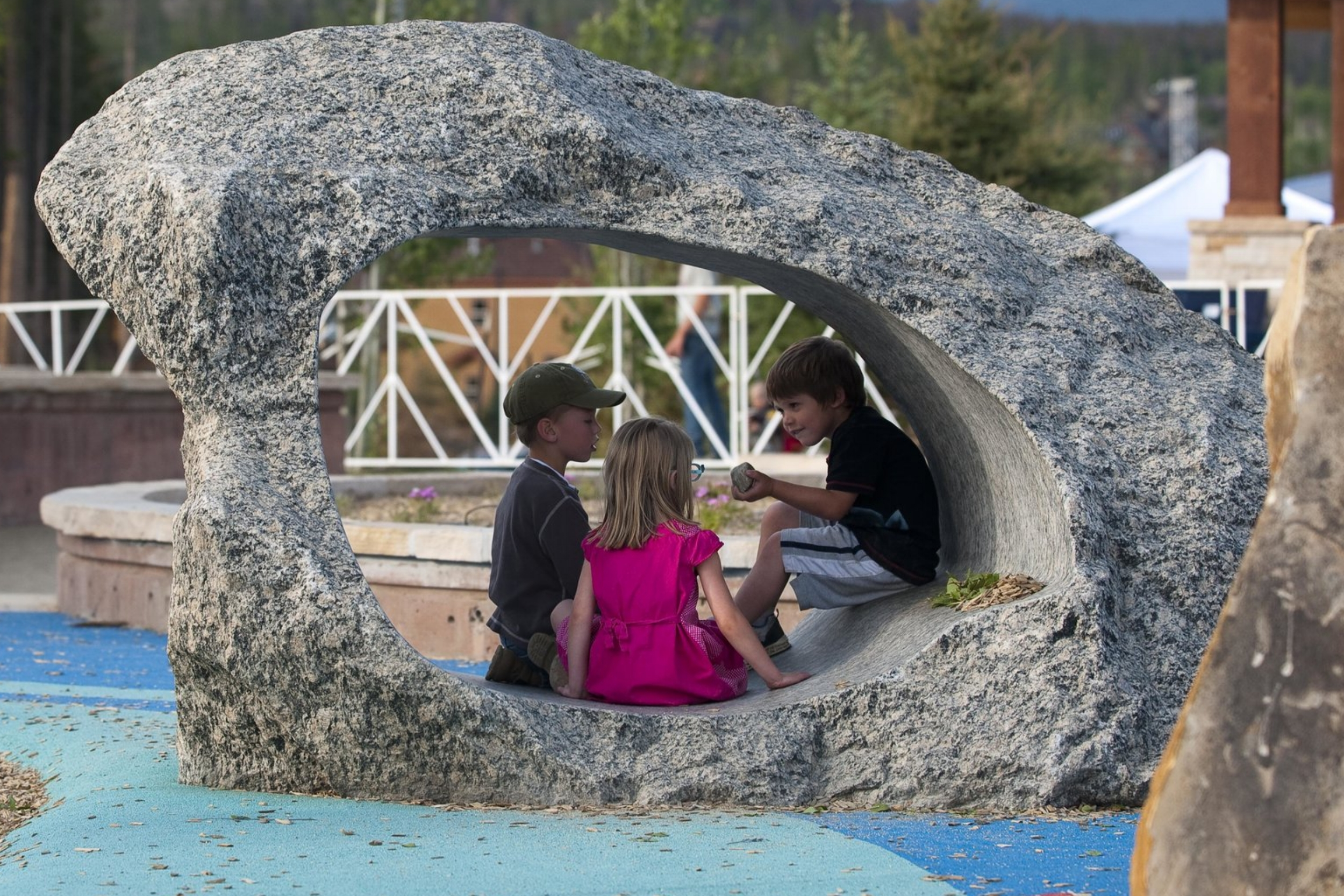 Kids exploring and having an adventure social in a boulder rock playground equipment