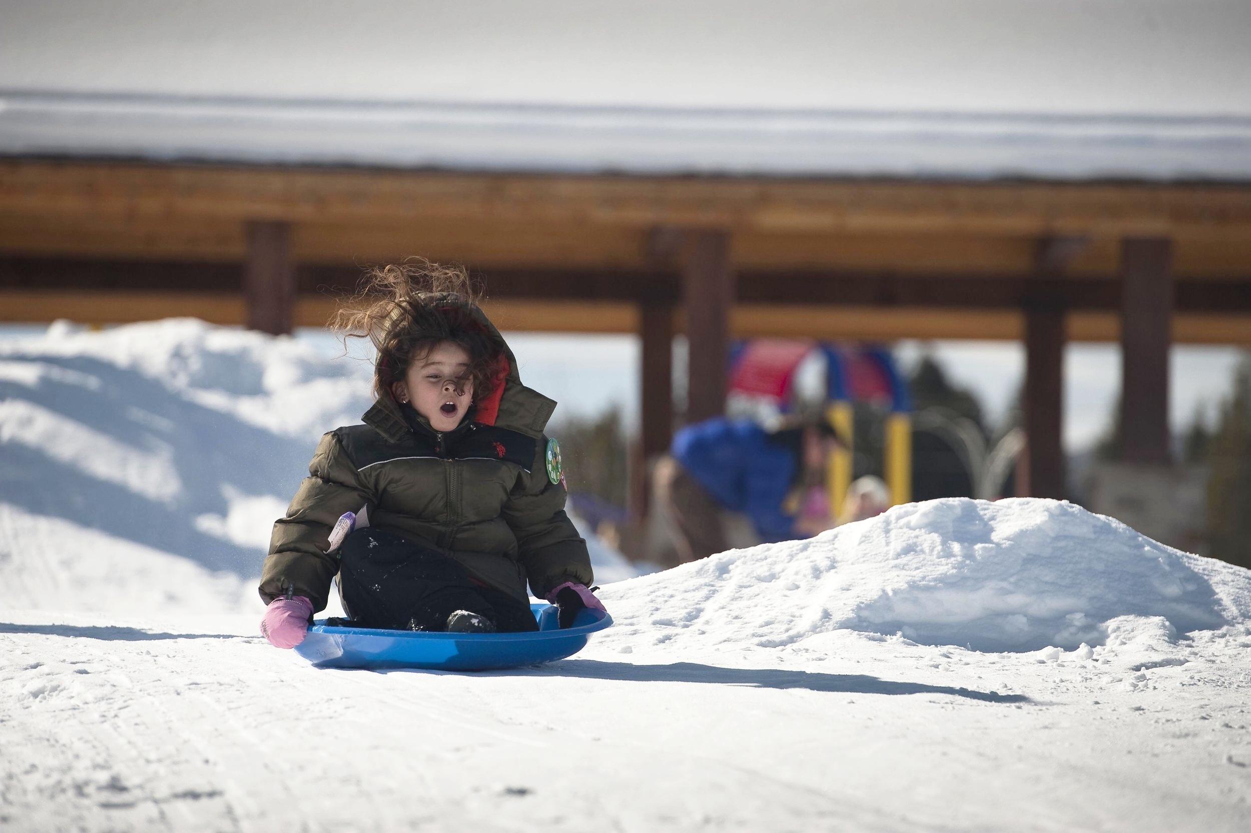 Girl kid on snow sledding hill in winter park hideaway concert festival venue amphitheater