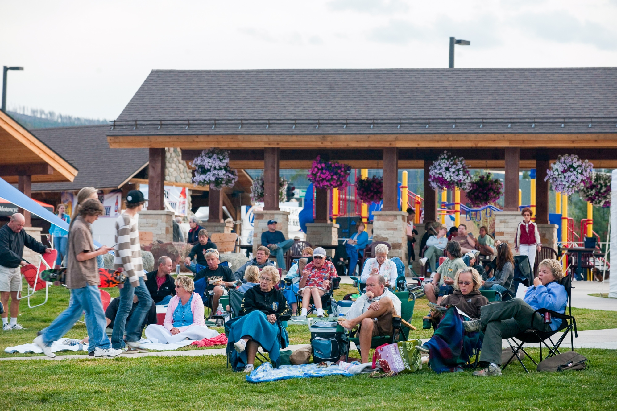 The audience of kids and adults await the music concert to begin playing in the amphitheater stage area