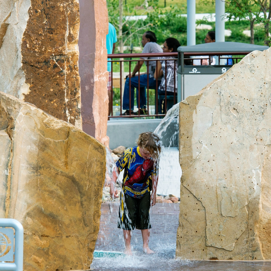 Boy getting head covered in water to help cool down at a top Colorado water park playground