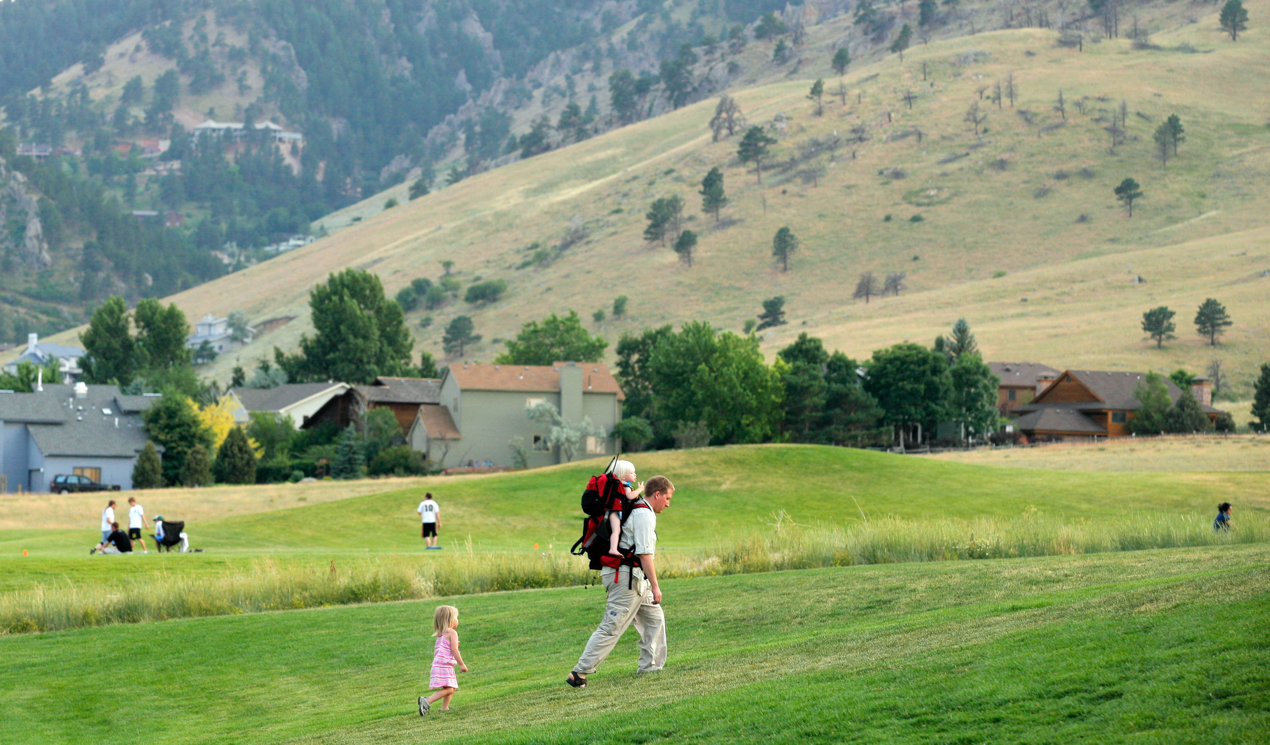 Dad hiking with kid in backpack and child following on a trail in a park surrounded by mountains.