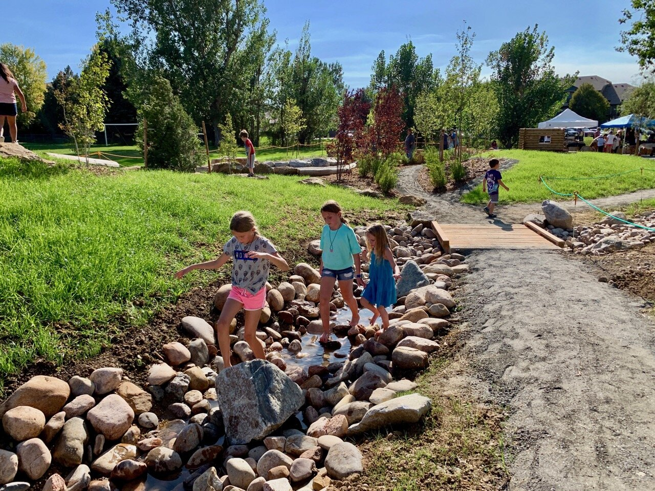 A great example of nature play is these kids splashing through a stream water feature at Nature Discovery Area & Inspire Trail in Lafayette, Colorado