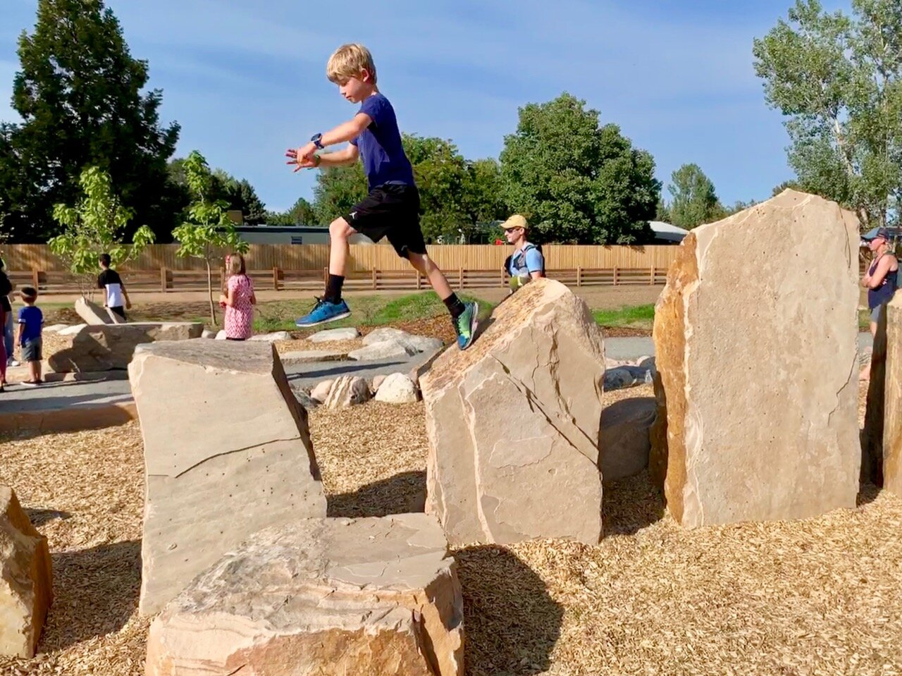 Kids jumping across boulders in the play area