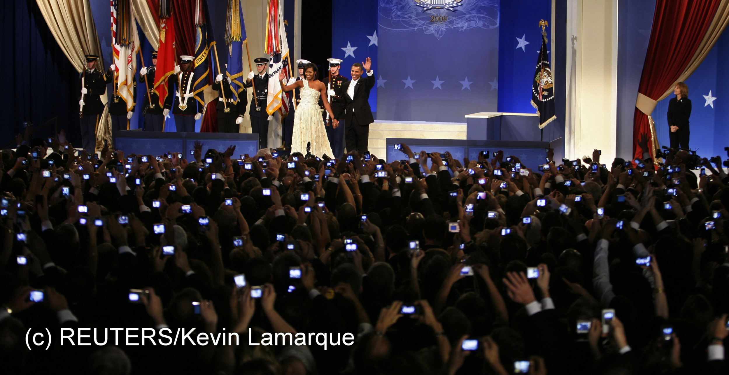 President Barack Obama and first lady Michelle wave to the crowd at the Home States Ball as audience members take pictures with their mobile phones in Washington January 20, 2009. Kevin Lamarque/REUTERS