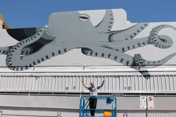 Artist Jordan Andreotta with his Octopus painting on the old Salvation Army building.