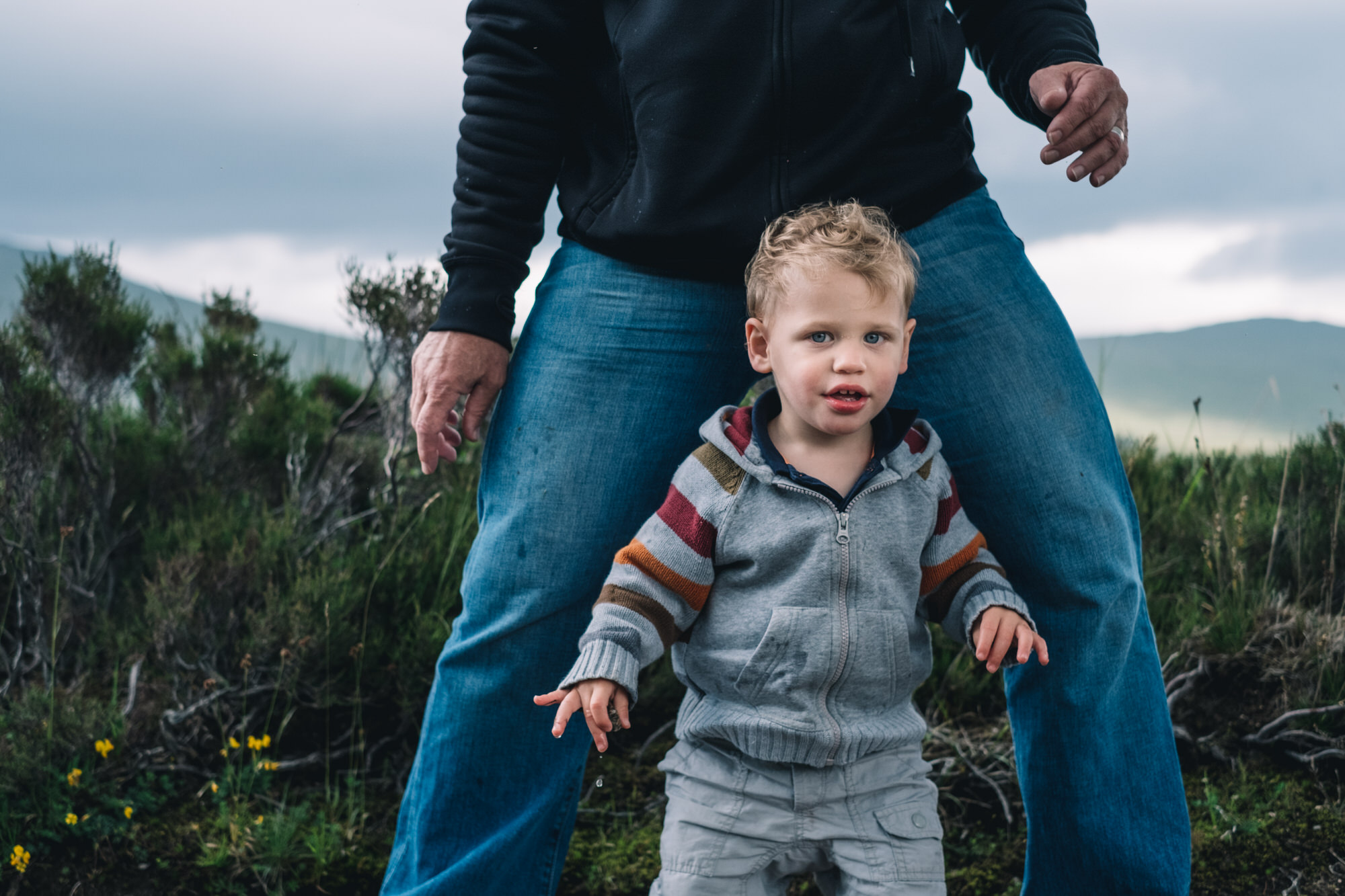 Son stands between his father's legs