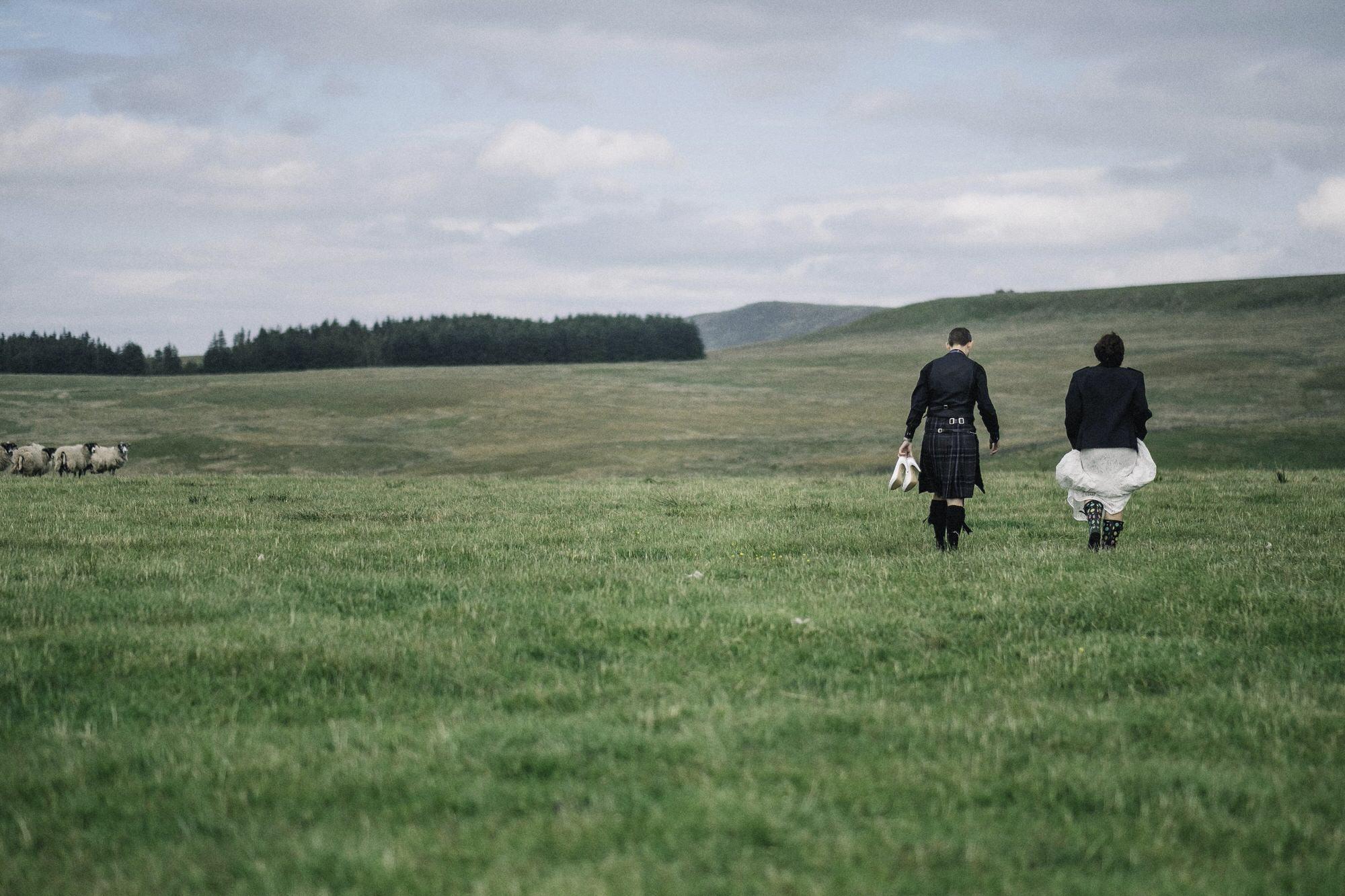 Bride + groom walking in a field
