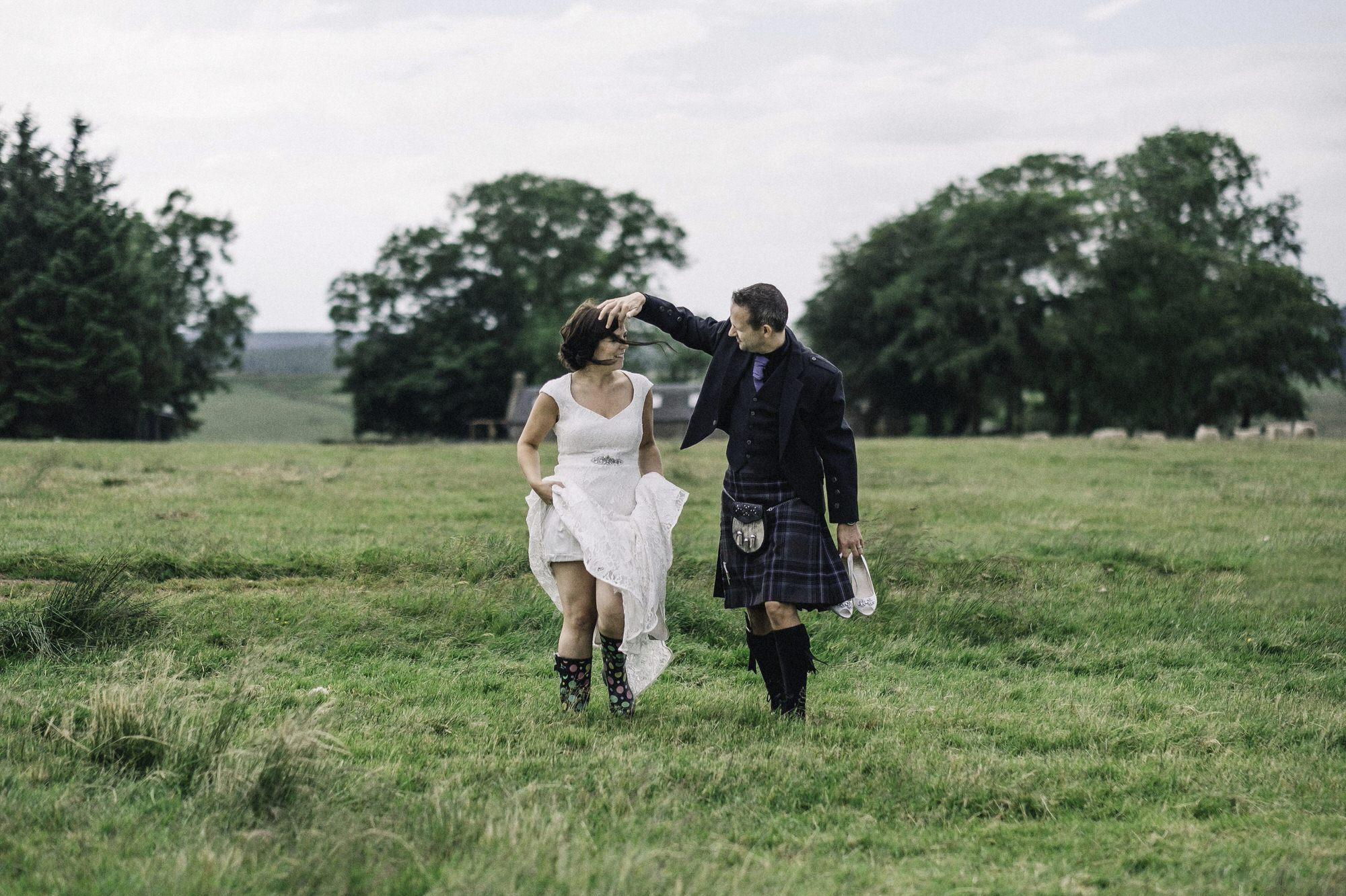 Bride & groom walking in a field