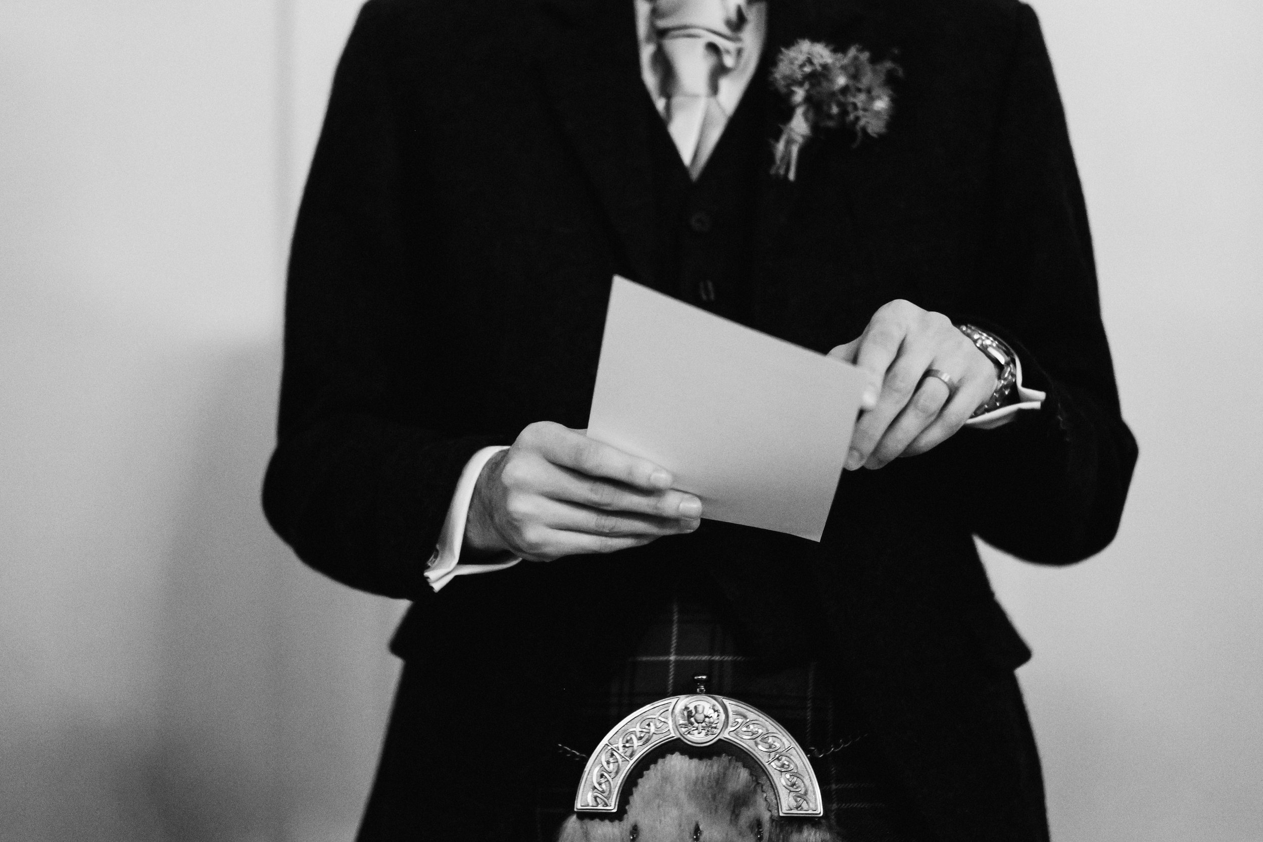 Groom holds notes for his speech