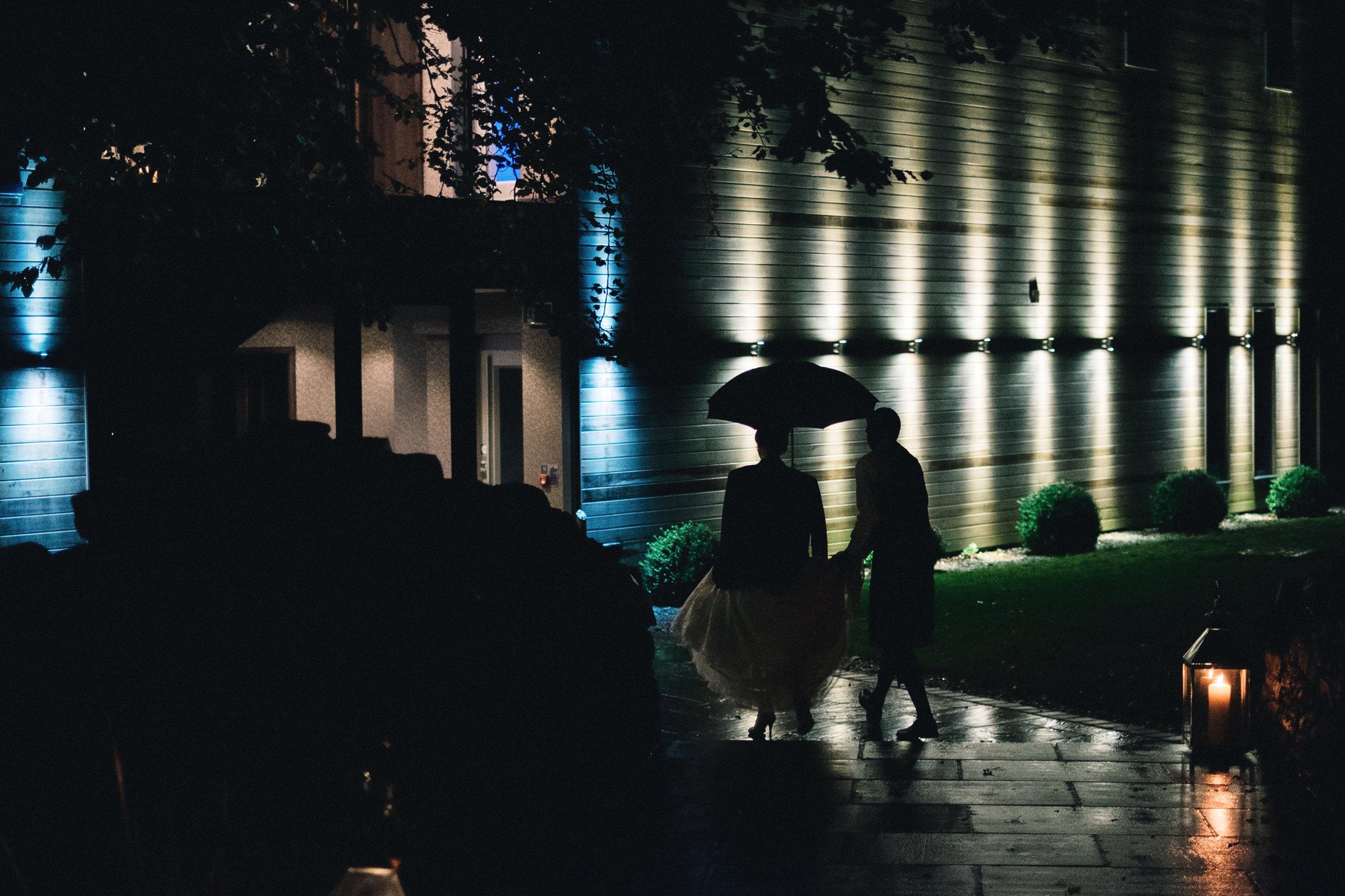 Bride and groom walk in the rain