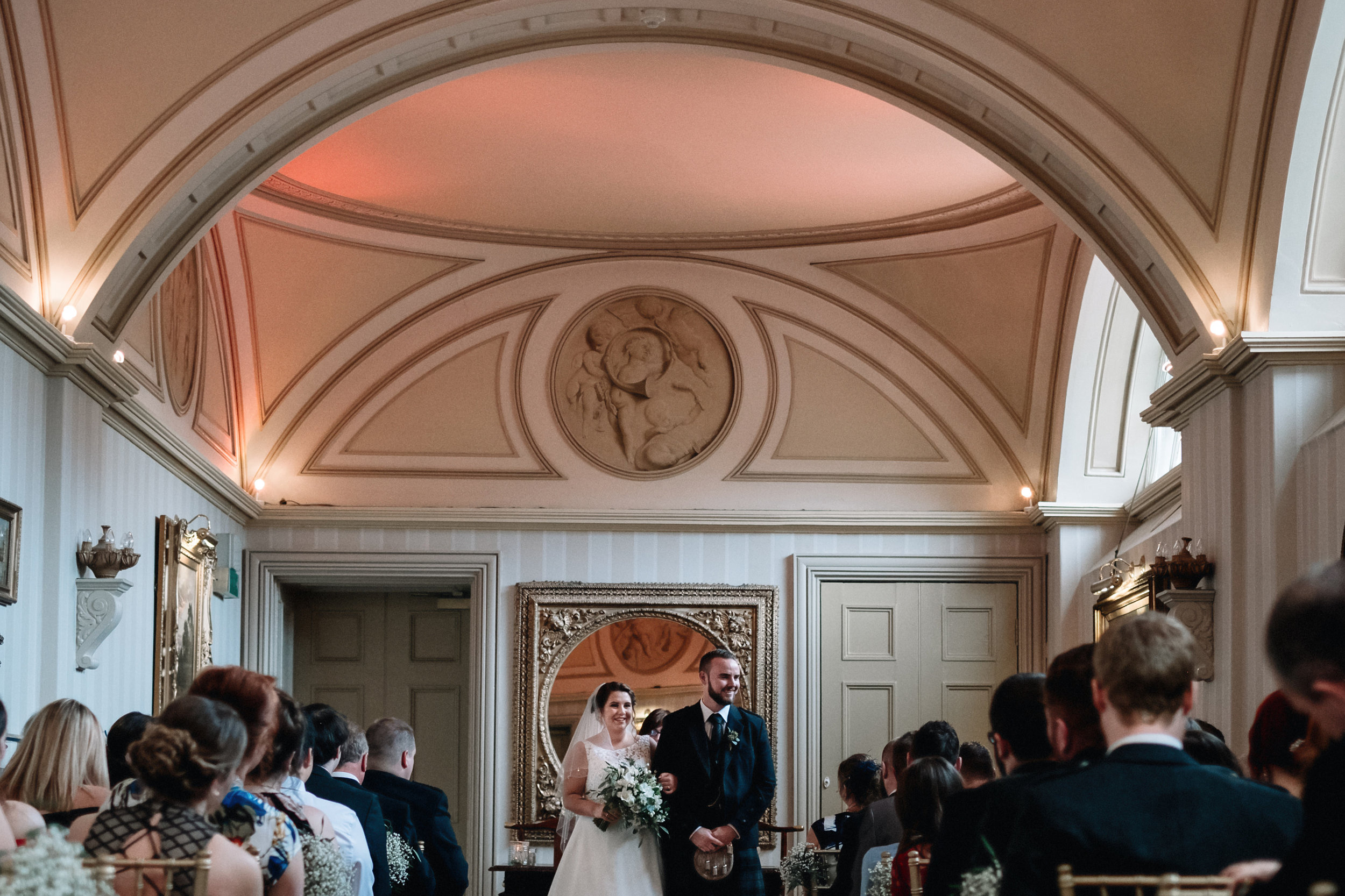 Bride and groom stand at the top of the aisle