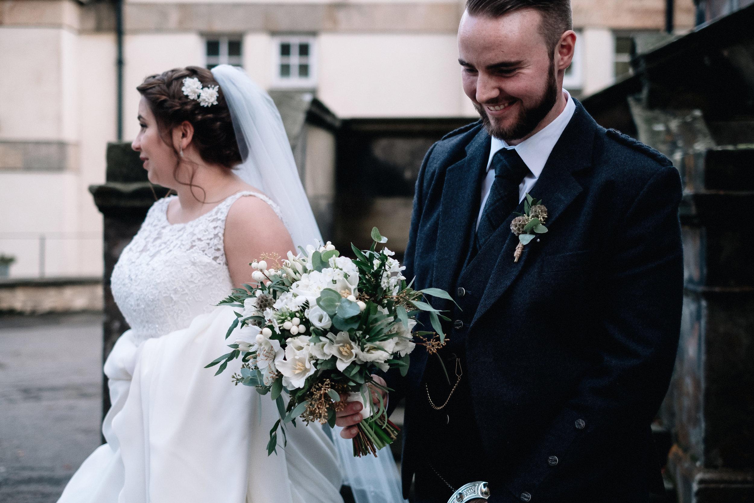Groom carries his bride's flowers