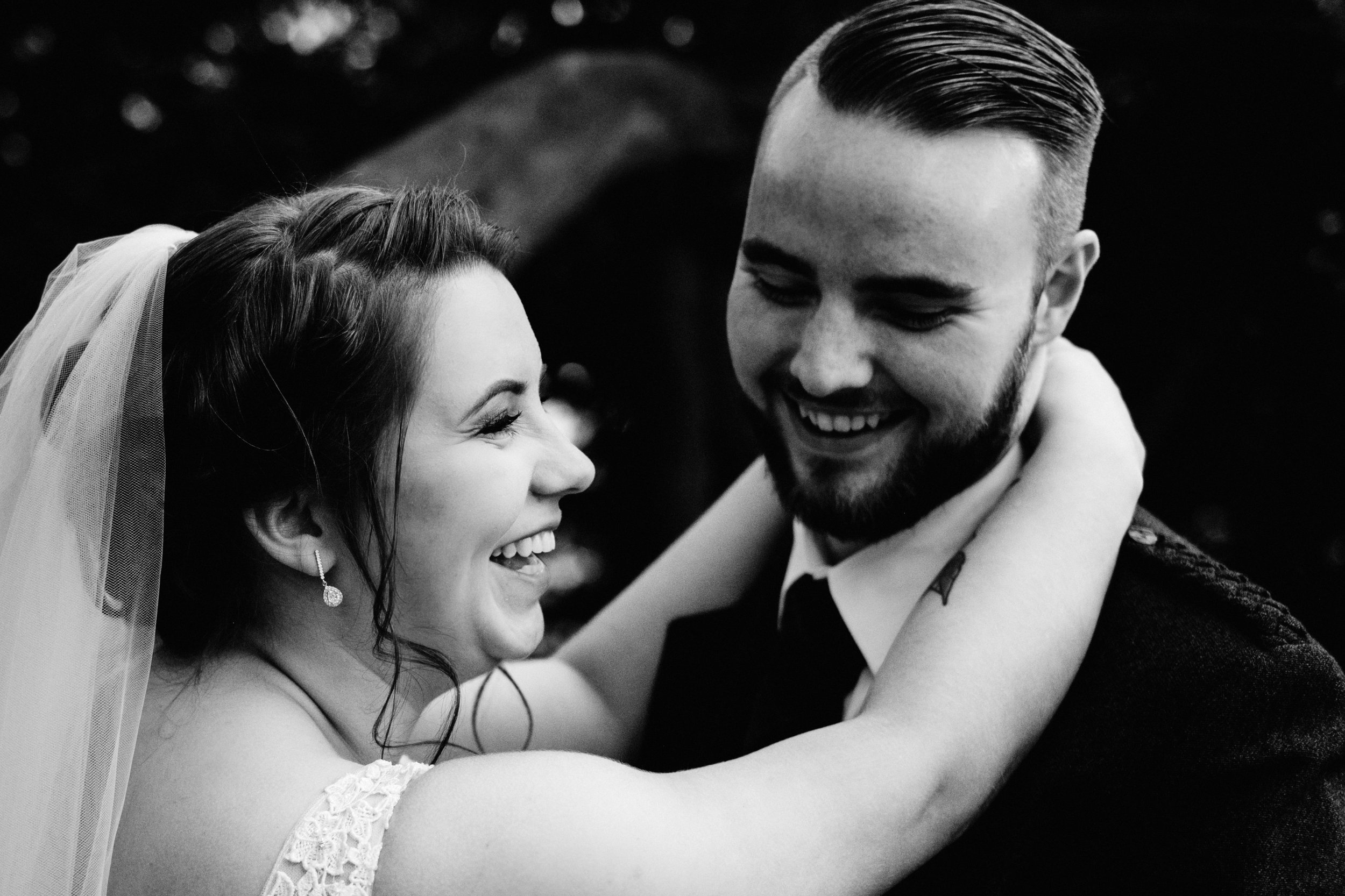 Bride and groom laugh in an embrace