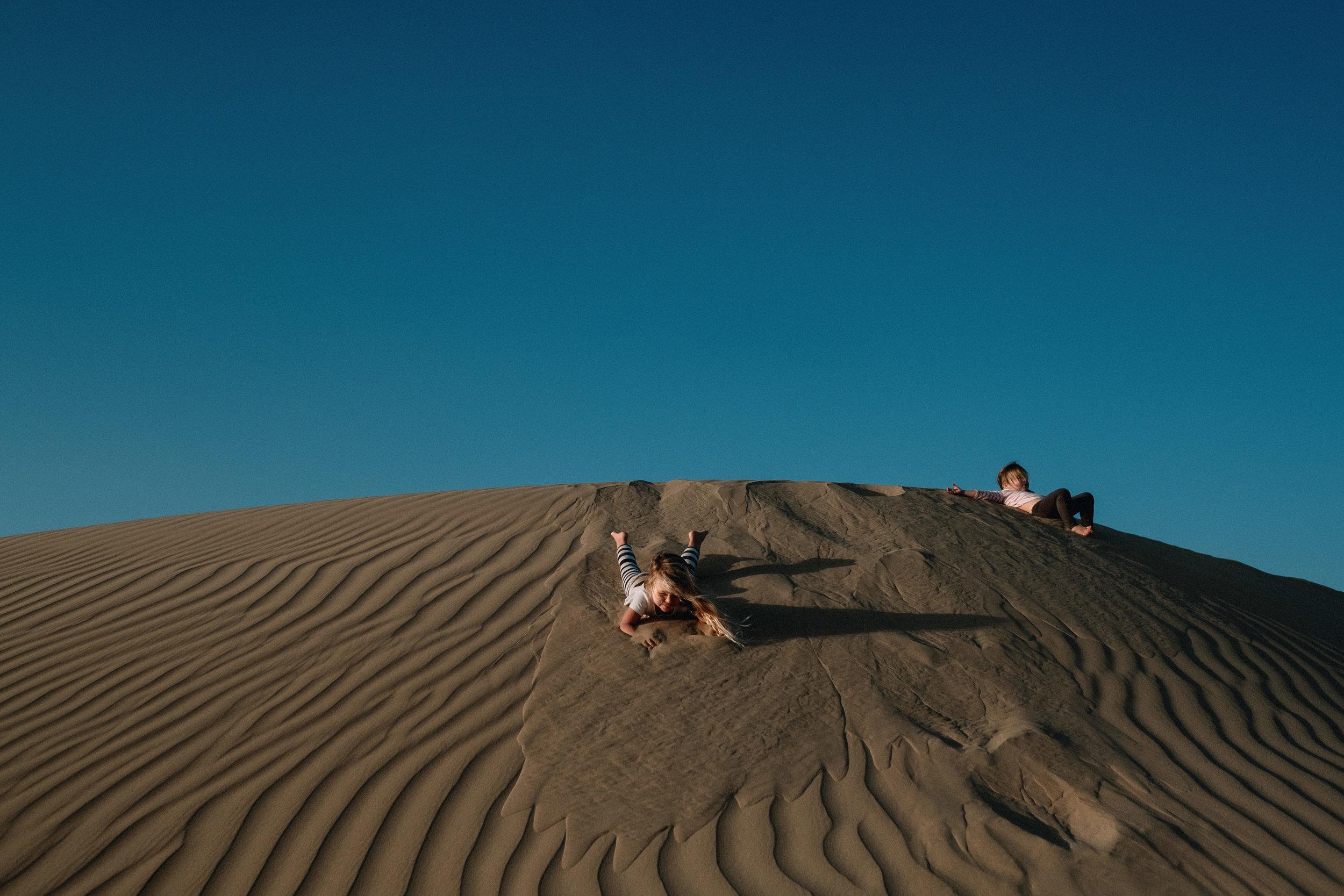 Three young girls slide down sand dune