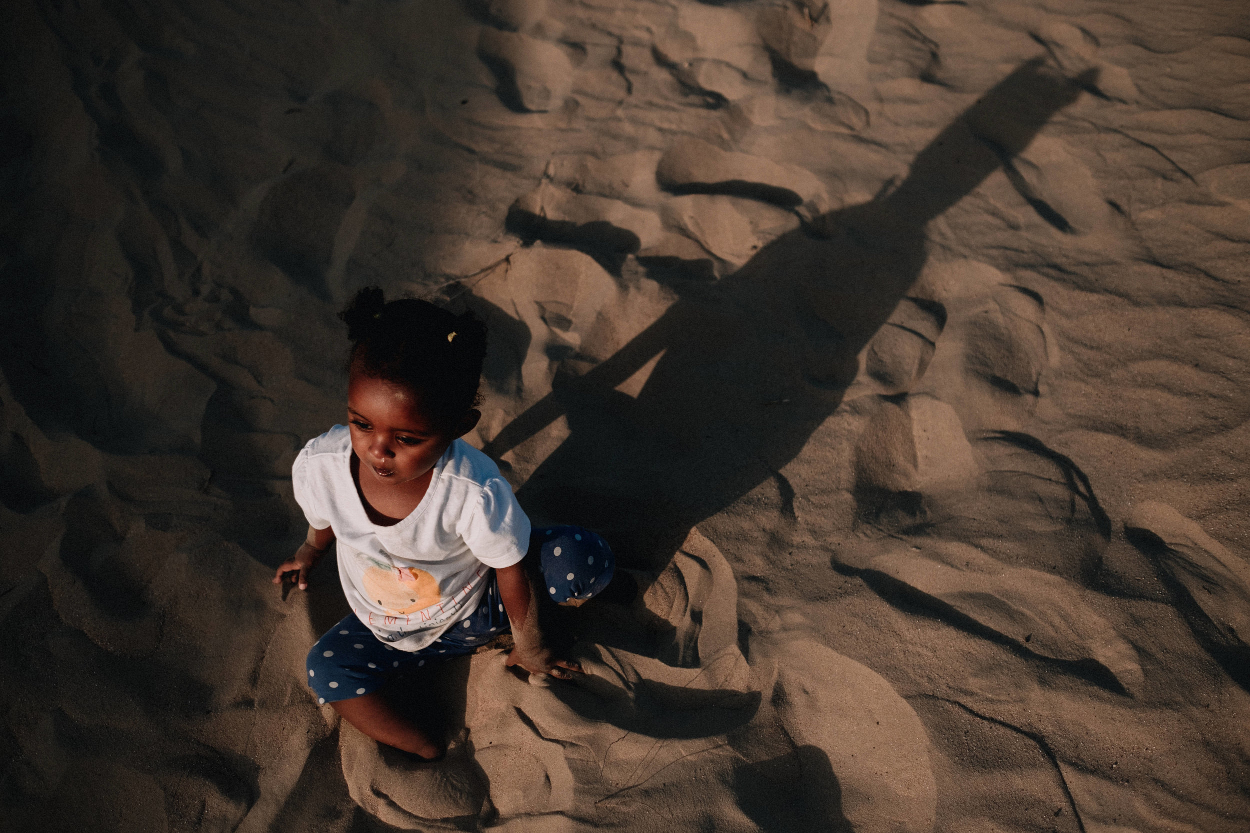 Young girl sitting in the sand