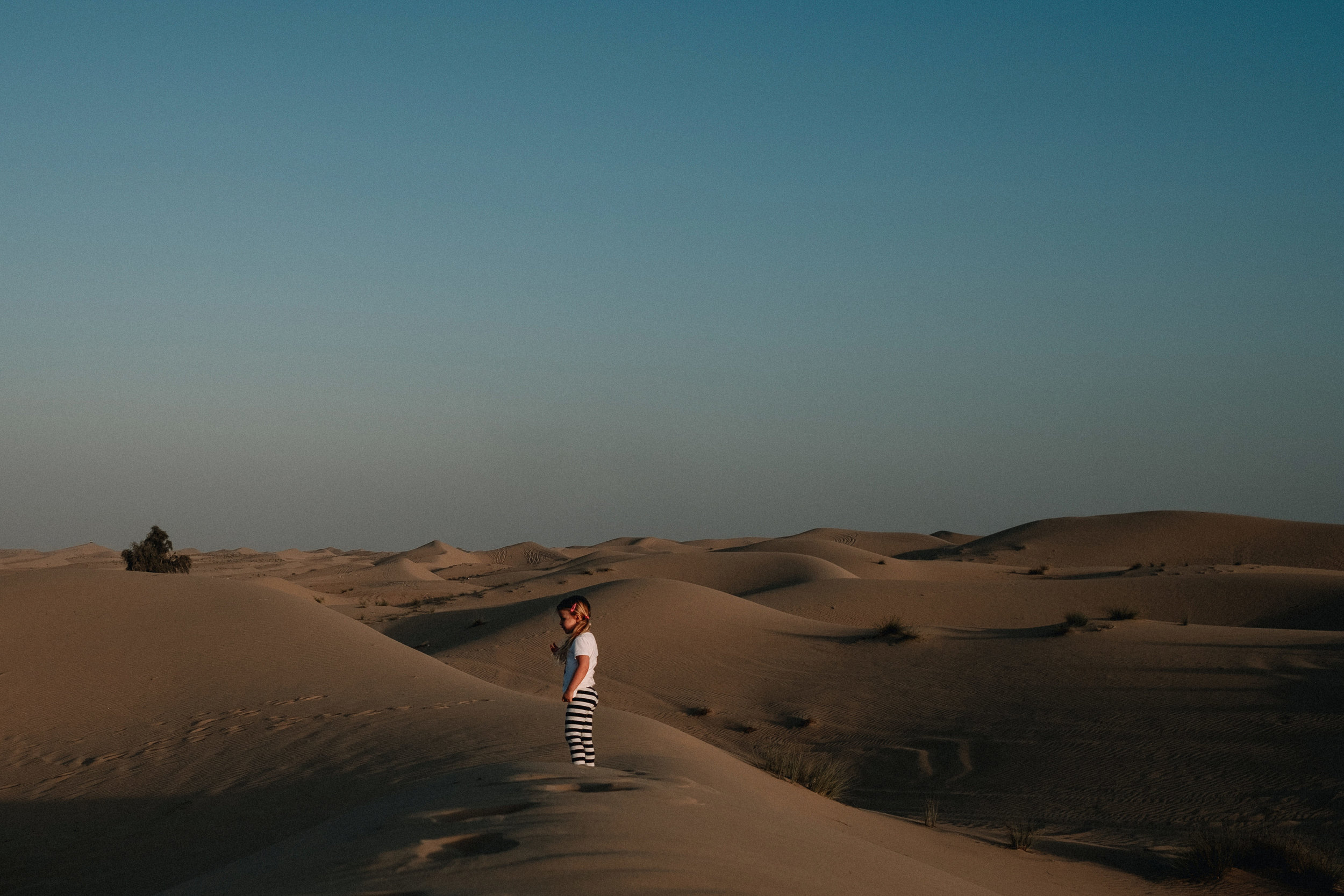 Young girl standing on top of a desert dune