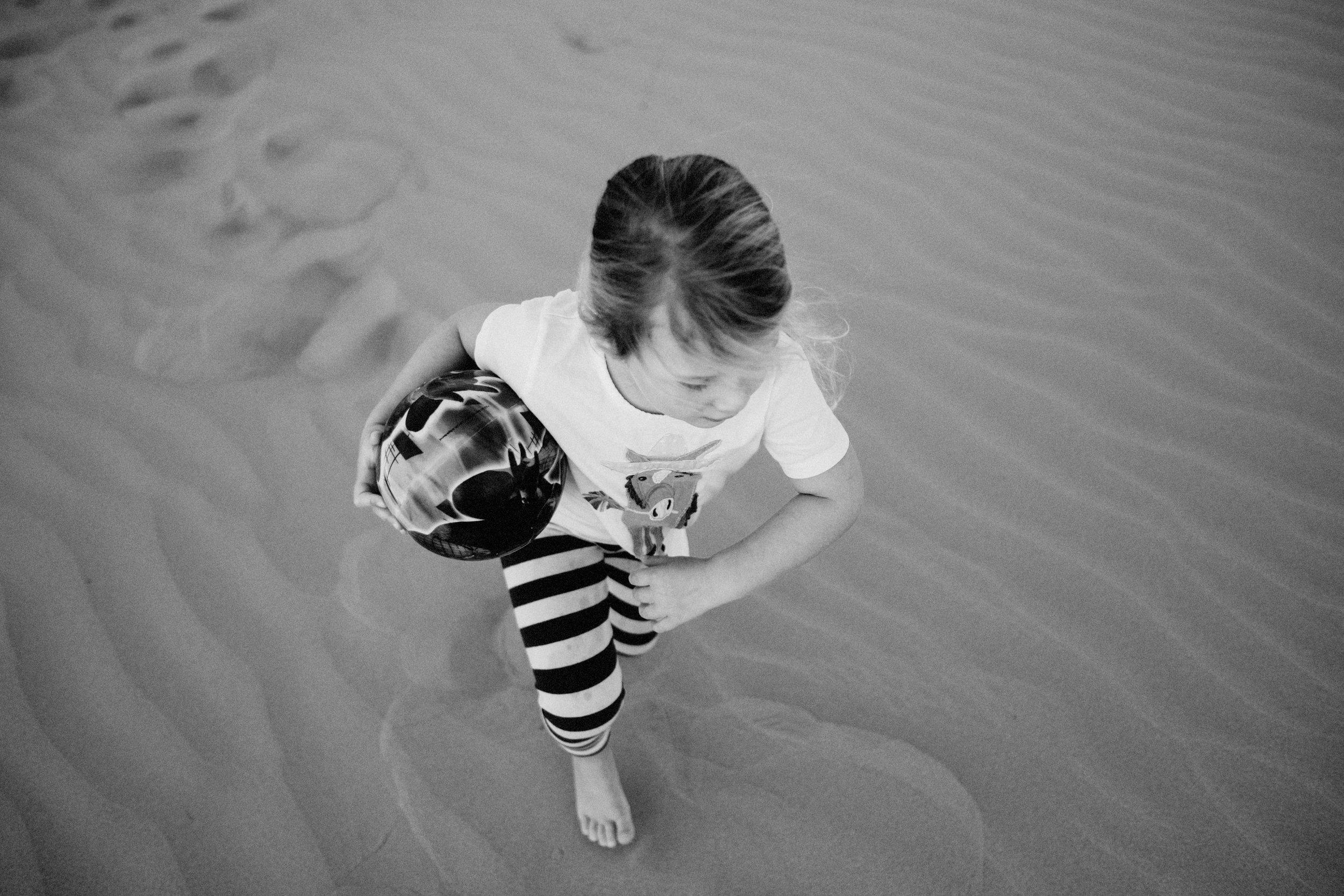 Girl runs on sand holding a ball