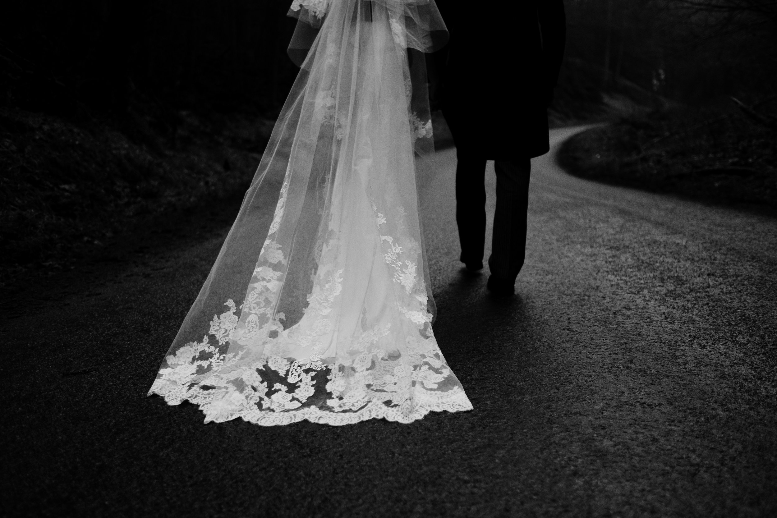 Bridal dress drapes along the wet ground