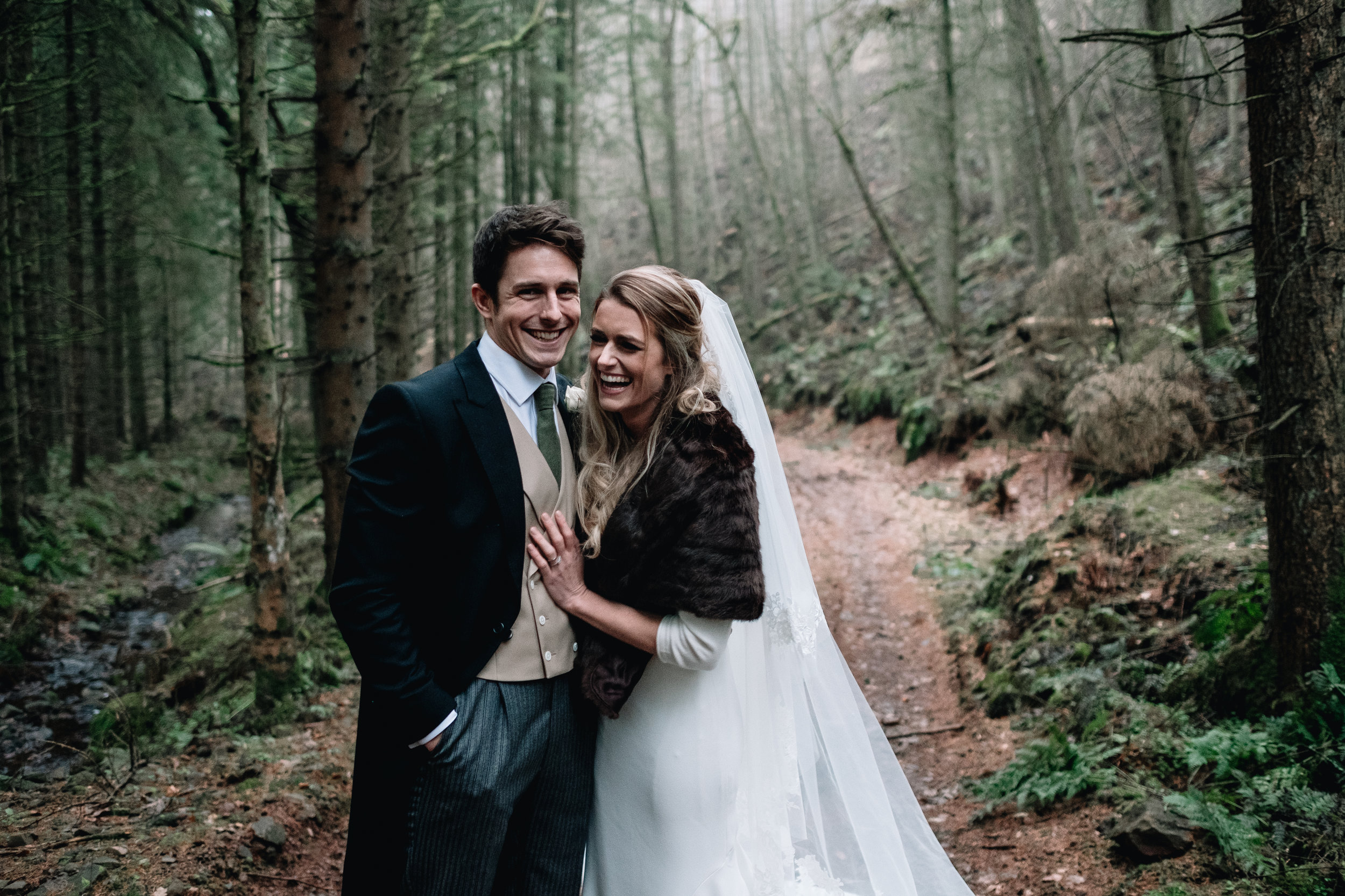 Bride and groom standing, laughing in a forrest