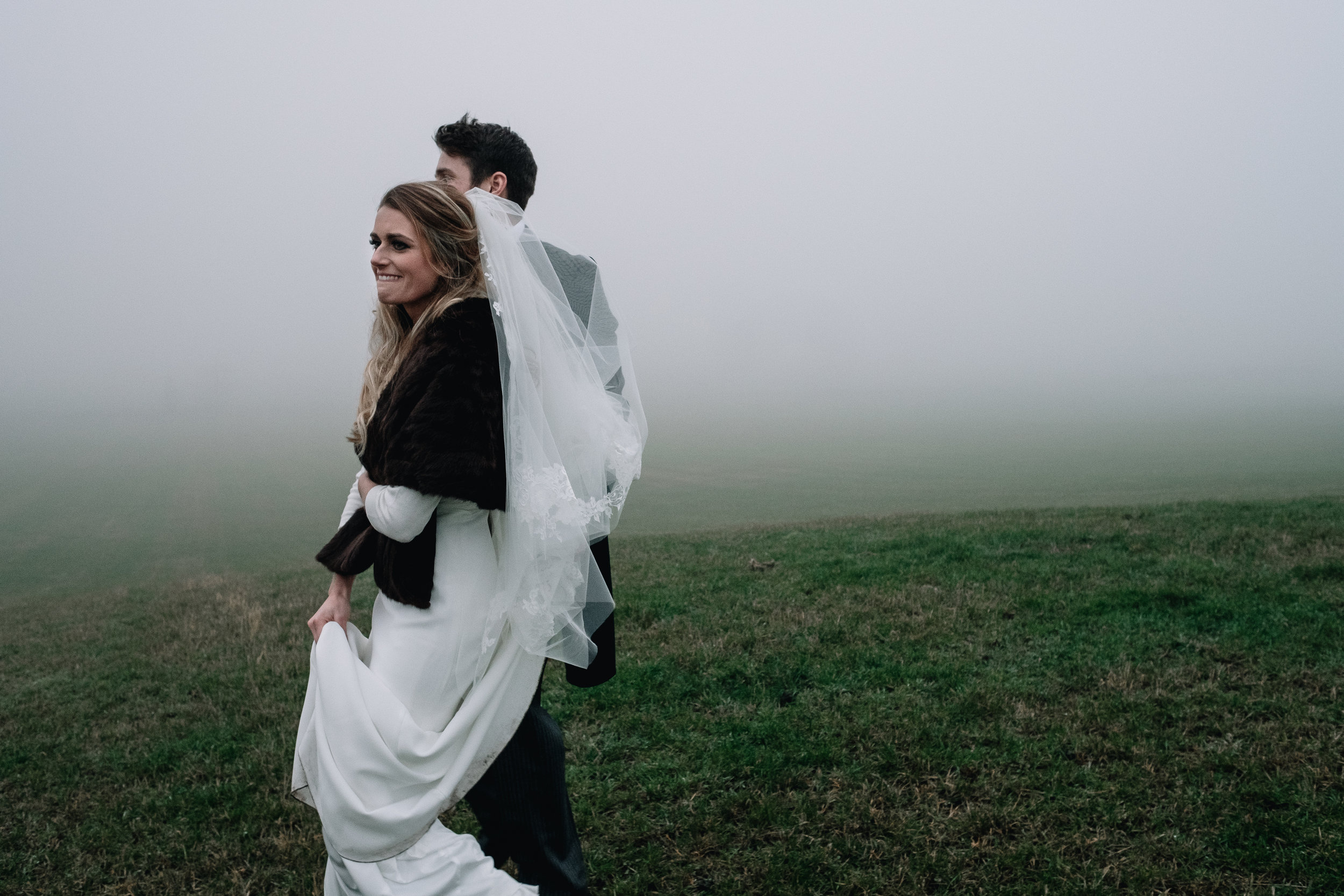 Bride and groom walking down a hill