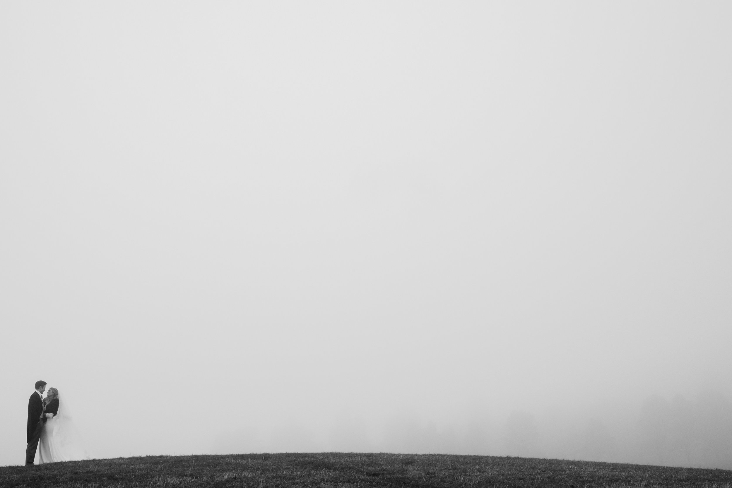 Couple standing on top of a mountain in the fog