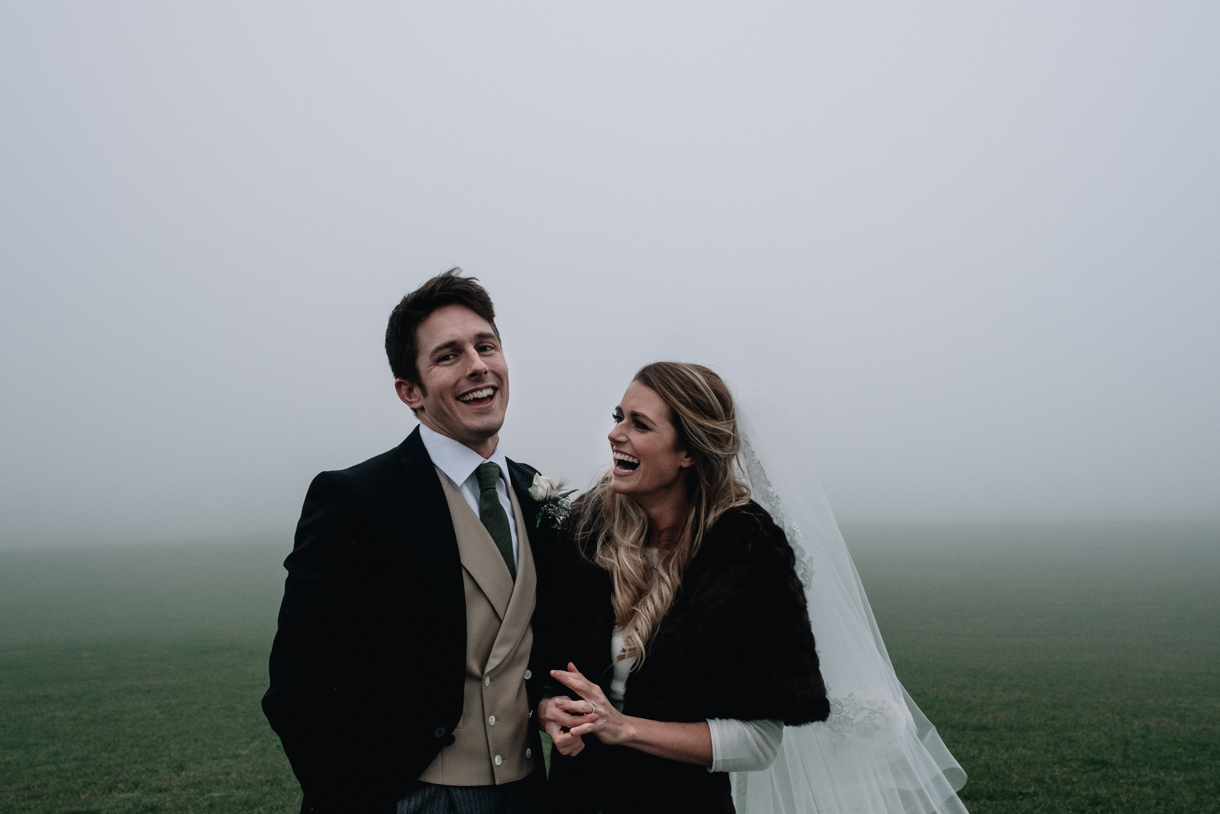 Bride and groom standing in the middle of a field
