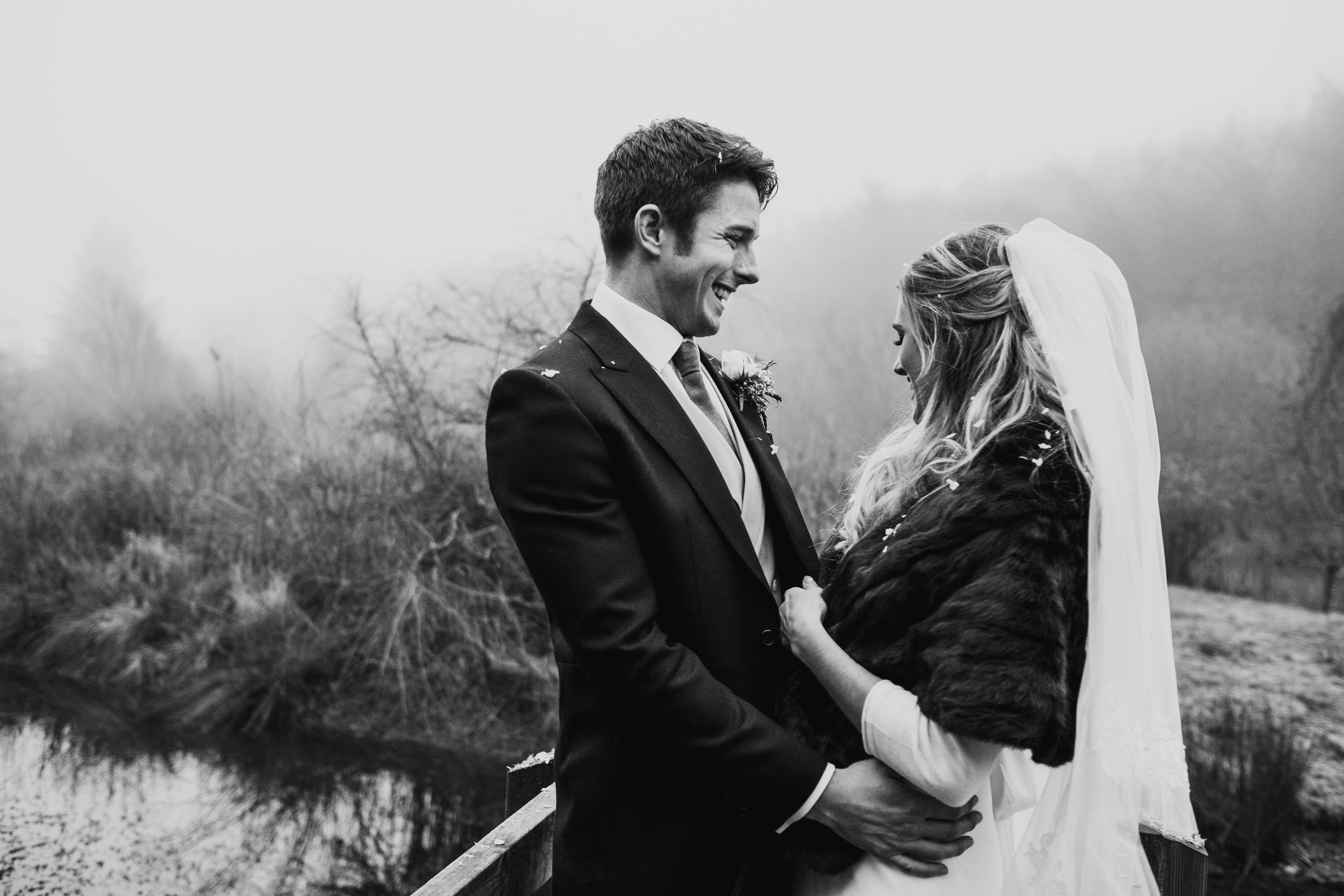 Bride and groom embrace each other outside on a bridge