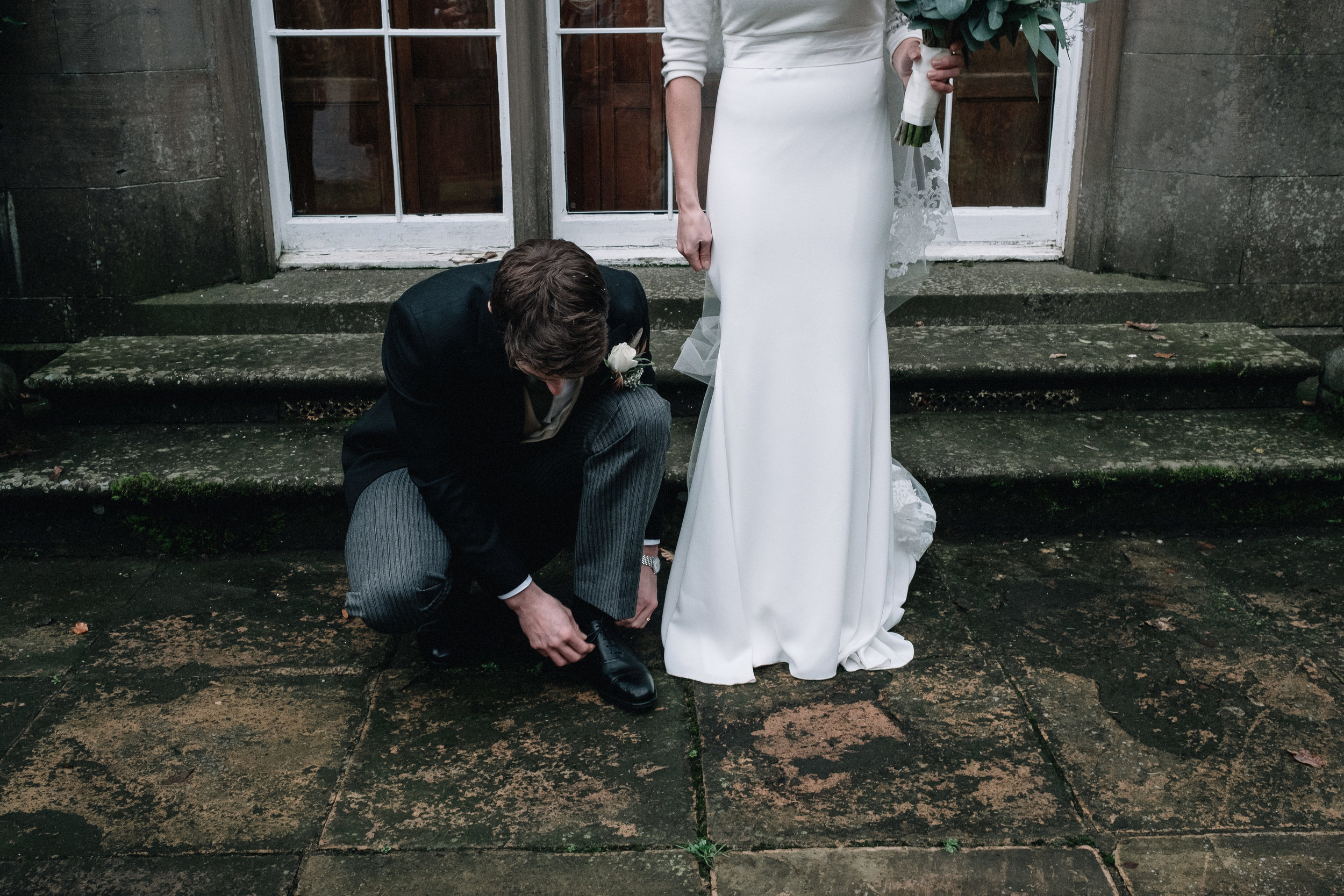A groom is kneeling down to tie his shoe laces.