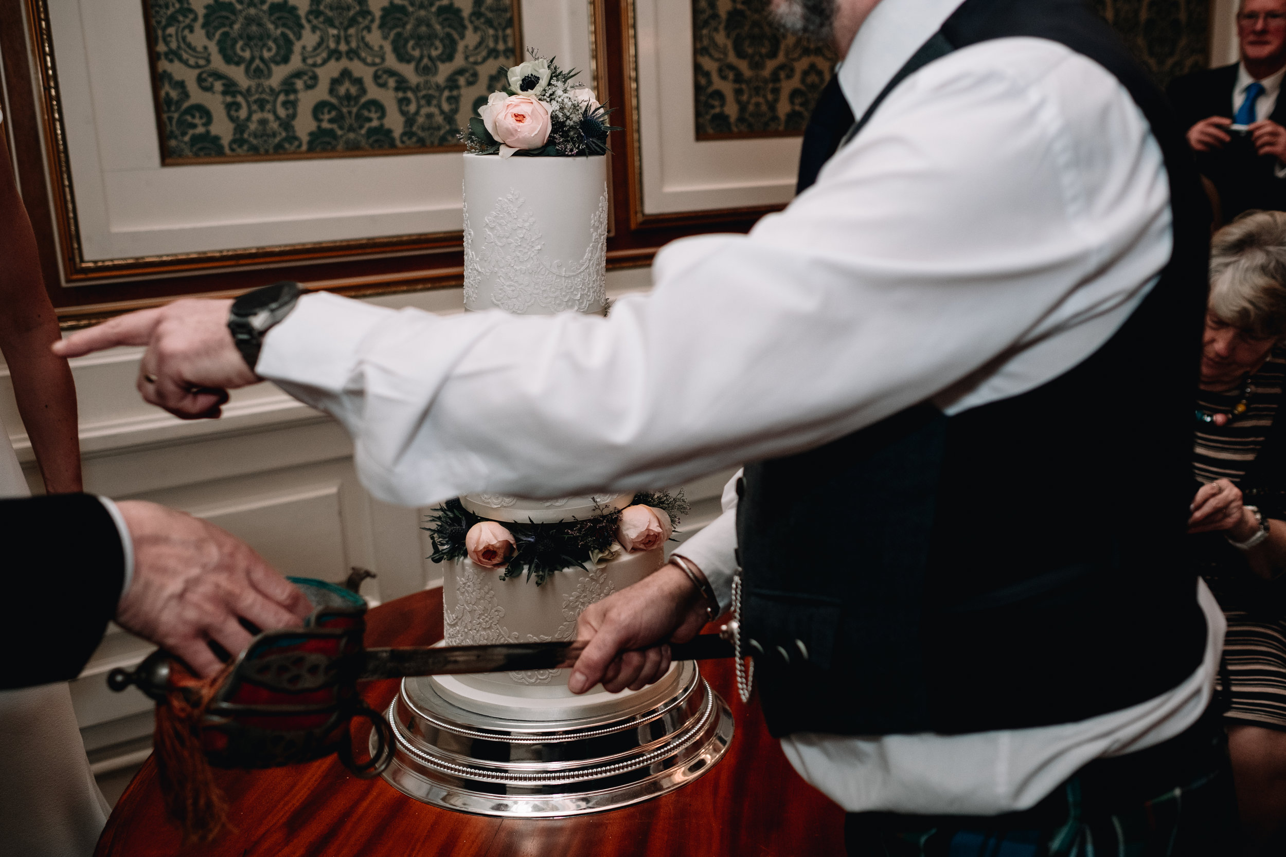 Knife being handed to groom for cake cutting