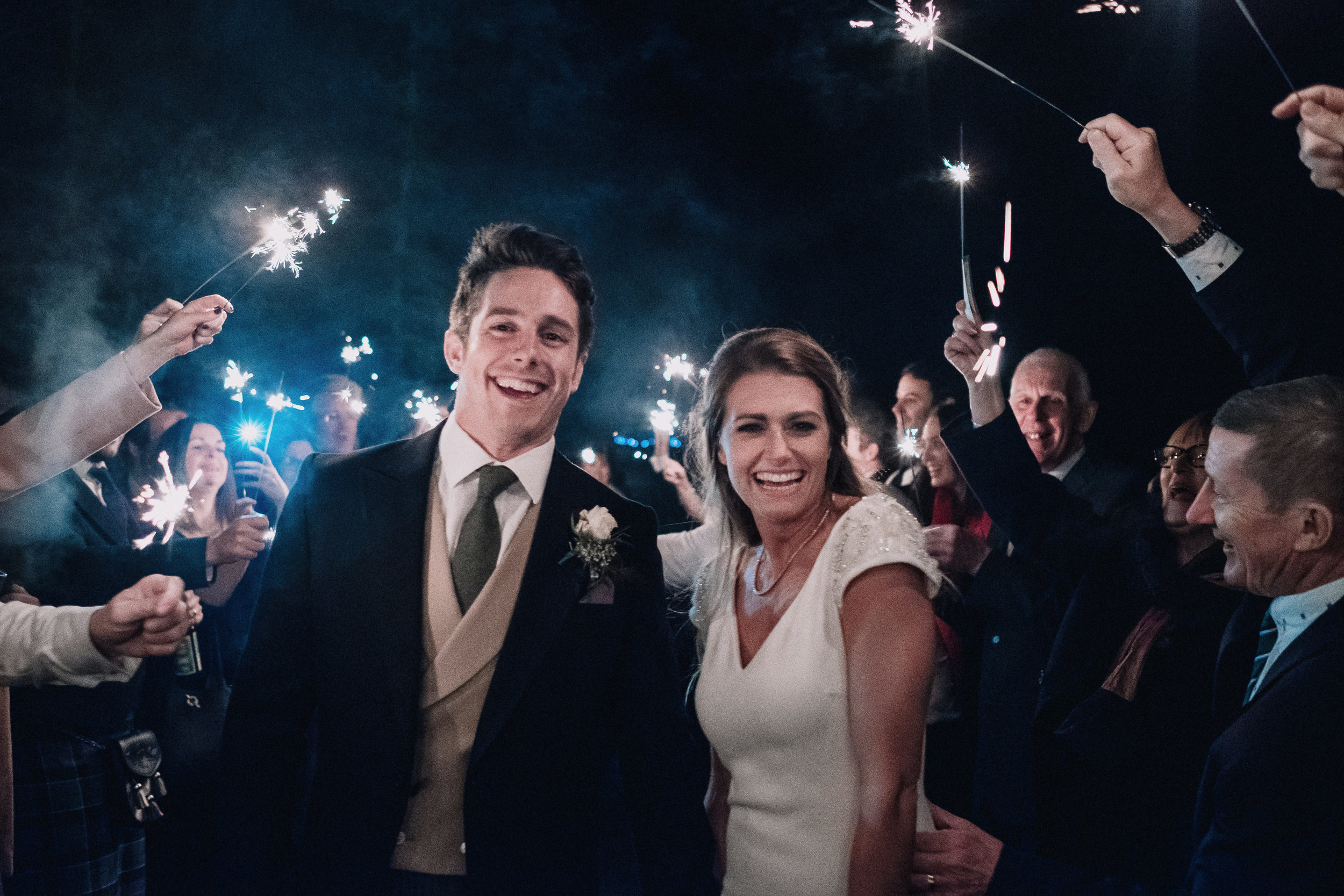 Bride and groom are surrounded by sparklers